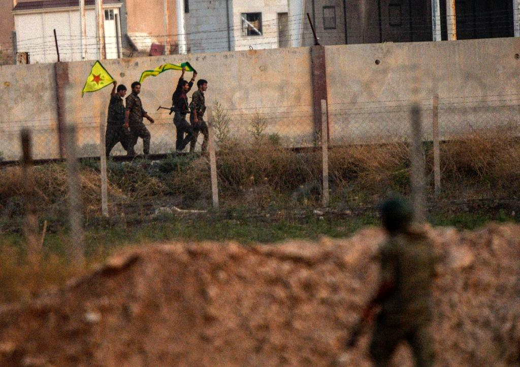 Kurdish People's Protection Units (YPG) fighters hold their movement's flag while a Turkish soldier looks at them near the Akcakale border crossing on June 15, 2015 (AFP Photo/Bulent Kilic)