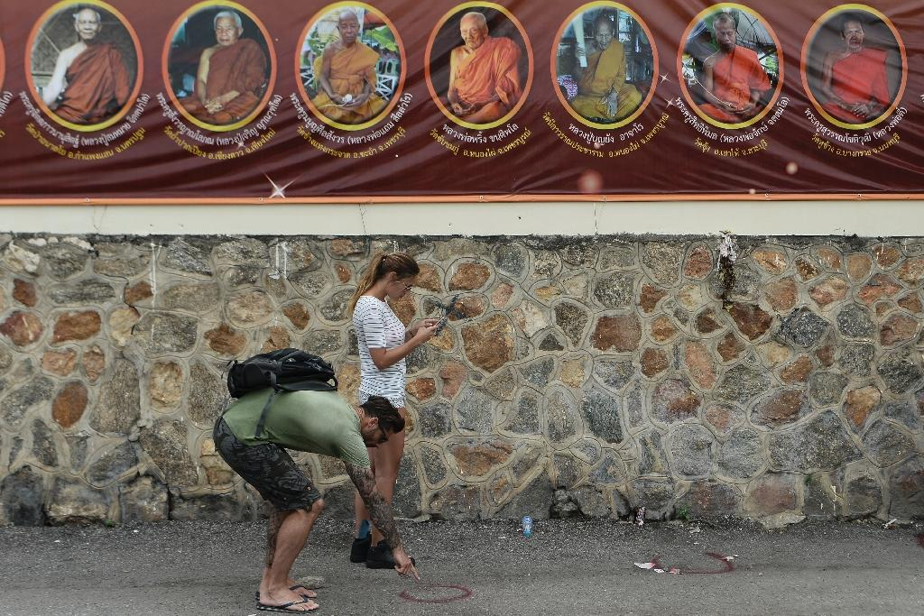 Foreign tourists look at the crime seen after a small bomb exploded in Hua Hin on August 12, 2016 (AFP Photo/Munir Uz Zaman)