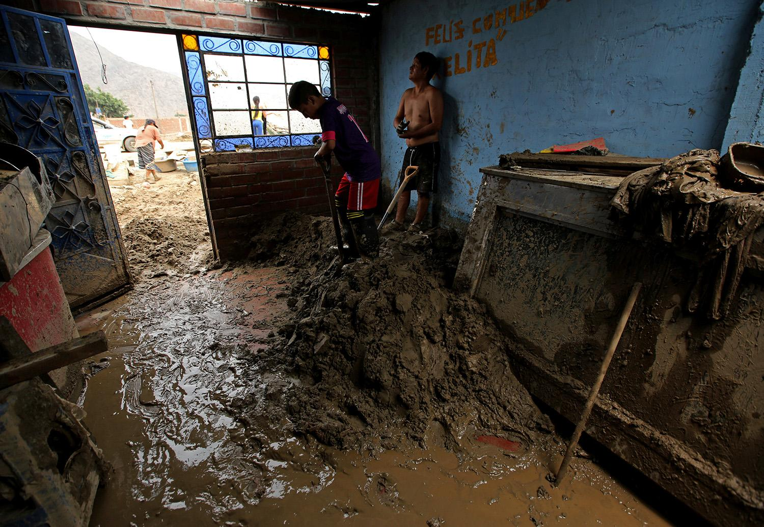 <p>Jairo Vargas, left, and Geremias Fuero clean their flooded home after rivers breached their banks due to torrential rains, causing flooding and widespread destruction in Huachipa, Lima,Peru, March 20, 2017. (Mariana Bazo/Reuters) </p>
