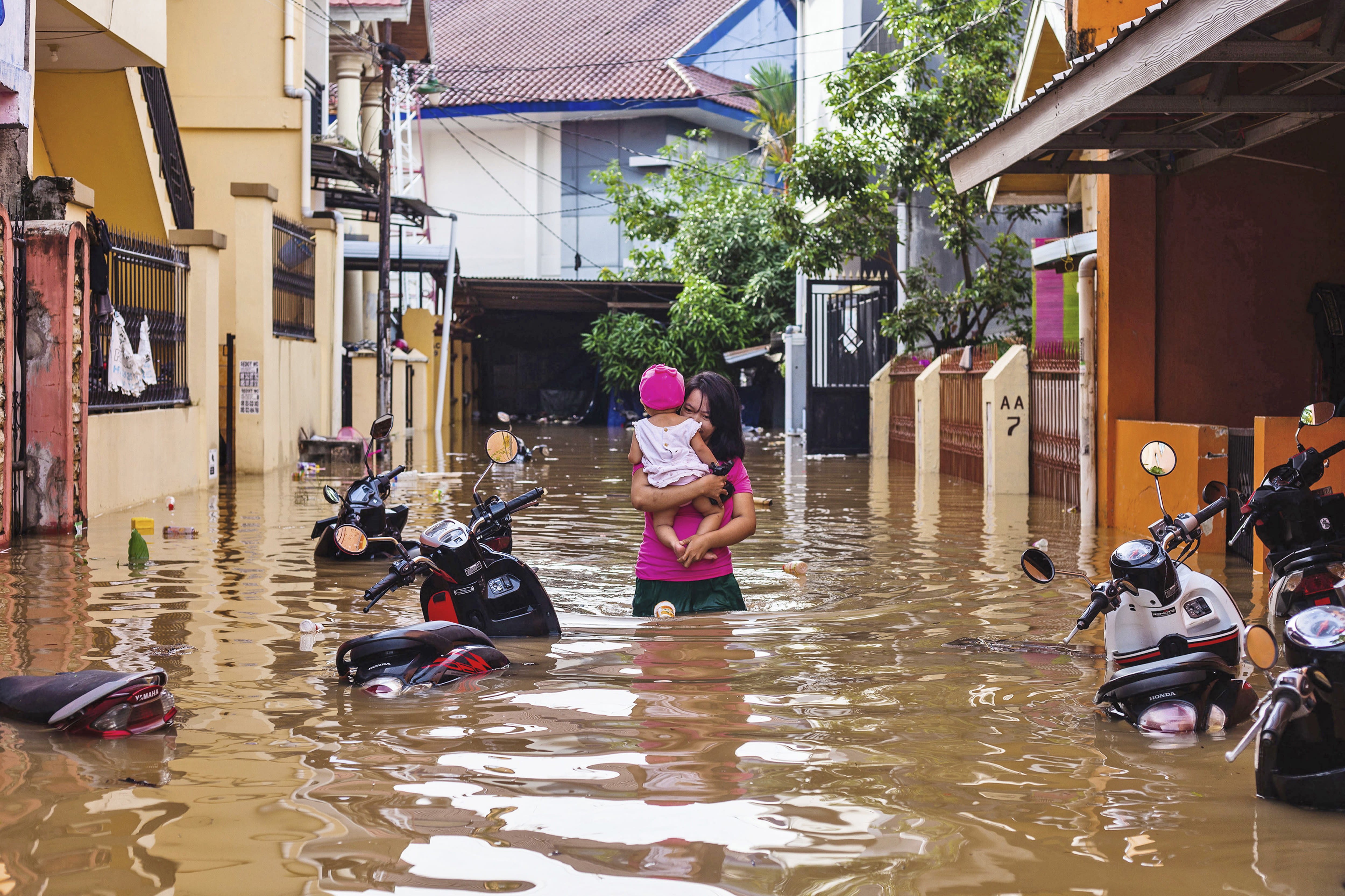 A woman carries her daughter as she wades through a flooded neighborhood in Makassar, South Sulawesi, Indonesia, Wednesday, Jan. 23, 2019. Torrential rains that overwhelmed a dam and caused landslides killed at least six people and displaced more than 2,000 in central Indonesia, officials said Wednesday. (AP Photo/Yusuf Wahil)
