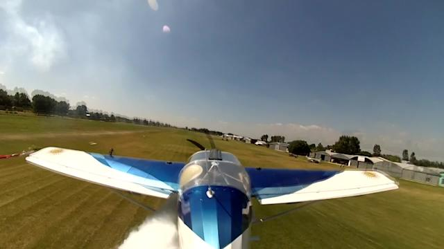 Low-flying plane picks up flags off the ground
