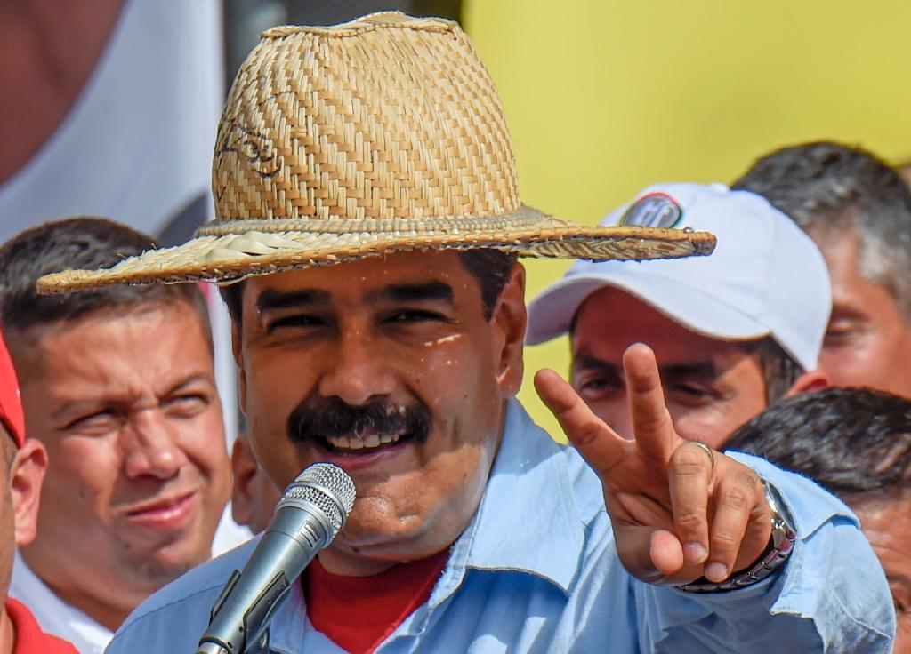 """Venezuelan President Nicolas Maduro flashes the """"V"""" sign during a rally in Caracas on May 31, 2016 (AFP Photo/Juan Barreto)"""