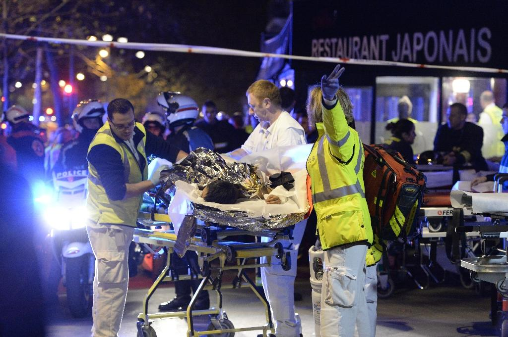 Rescuers evacuate an injured person near the Bataclan concert hall in central Paris, early on November 14, 2015 (AFP Photo/Miguel Medina)