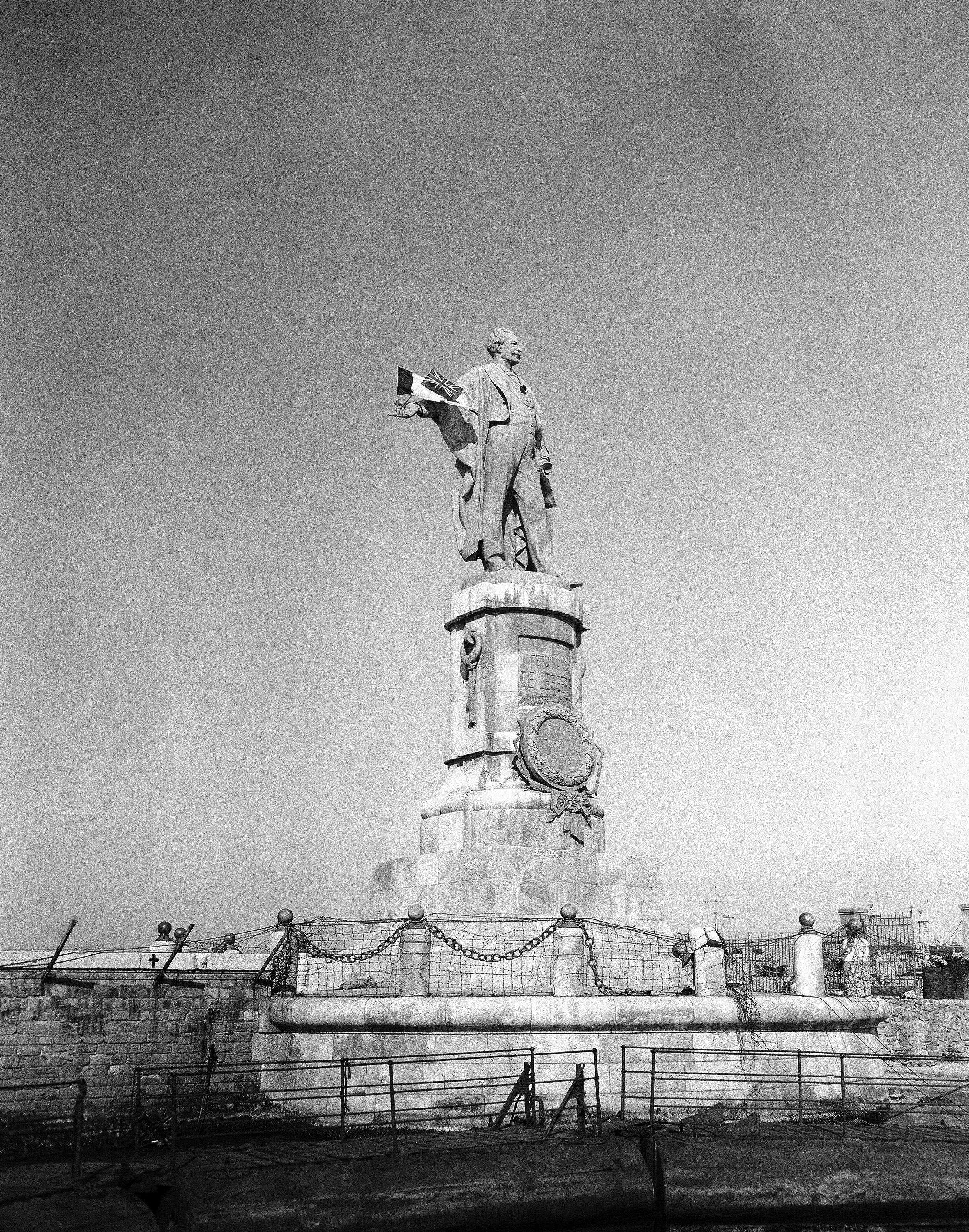 """FILE - This Dec. 22, 1956 file photo, shows the statue of Ferdinand de Lesseps, the French diplomat who was behind the construction of Egypt's Suez Canal, in the harbor of Port Said, Egypt. A proposal to bring back the statue has stirred controversy in Egypt with many saying it would be a salute to colonial times and a """"humiliation"""" to the memory of tens of thousands of Egyptian laborers who died while digging the waterway. The debate started when a newspaper reported in June 2020 that local authorities in the Mediterranean province of Port Said were thinking of returning the statue to where it once stood at the northern entrance of the canal. (AP Photo/Jim Pringle, File)"""