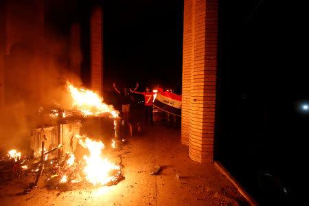 Iraqi protesters gesture near the burnt Iranian Consulate in Basra, Iraq September 7, 2018. REUTERS/Essam al-Sudani