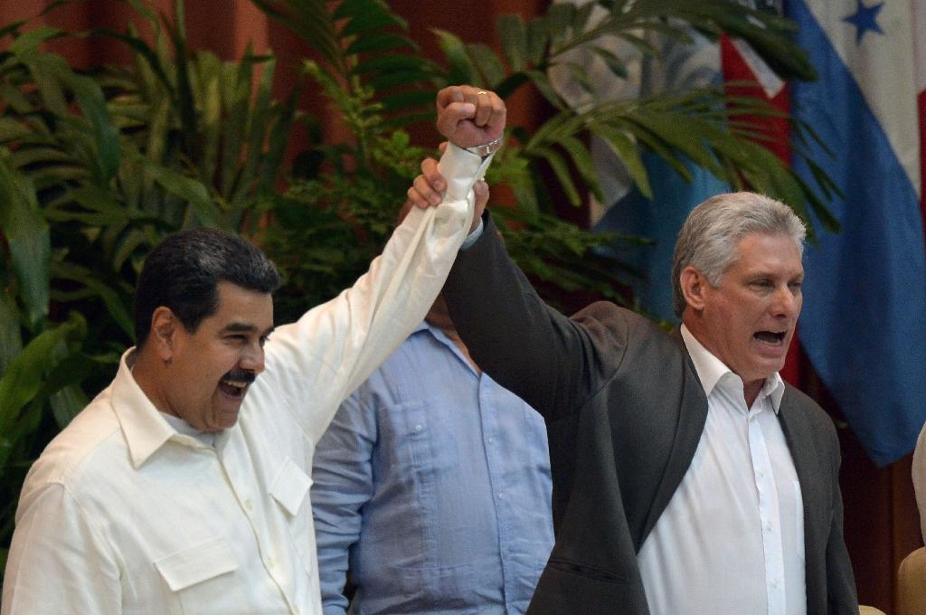 Cuban President Miguel Diaz-Canel, in navy jacket, seen with Venezuelan President Nicolas Maduro, says Cuba's looming recognition of a market economy does not mean capitalism is welcome