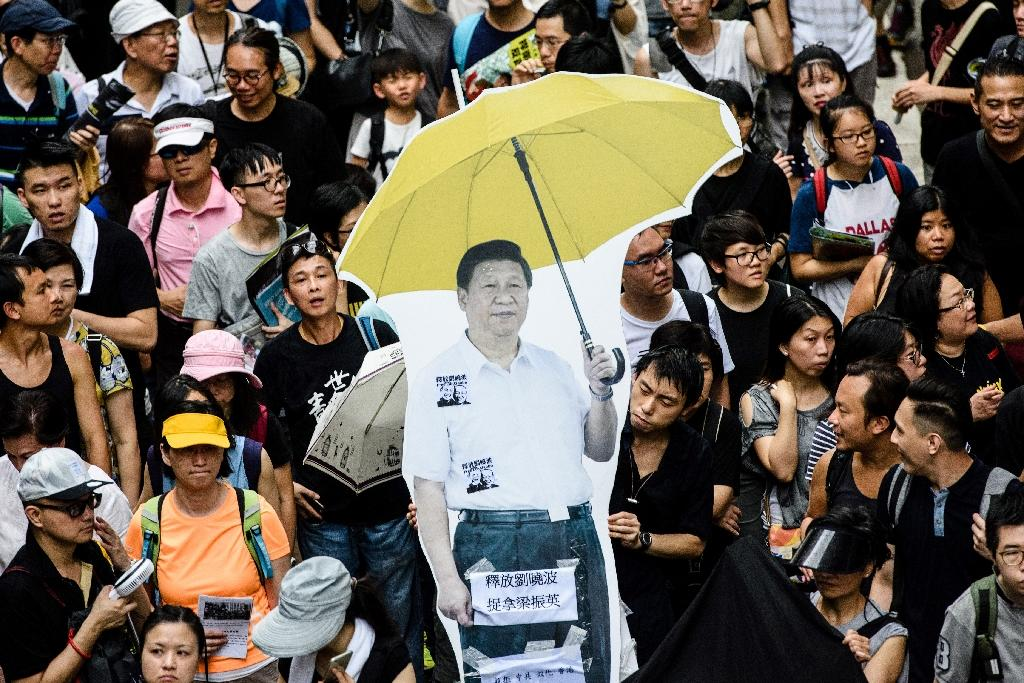 A cardboard cut-out of China's President Xi Jinping holding a yellow umbrella, a symbol of the 2014 'Umbrella Movement' is carried during a protest in Hong Kong on July 1 -- the 20th anniversary of the city's handover from British to Chinese rule (AFP Photo/Anthony WALLACE)