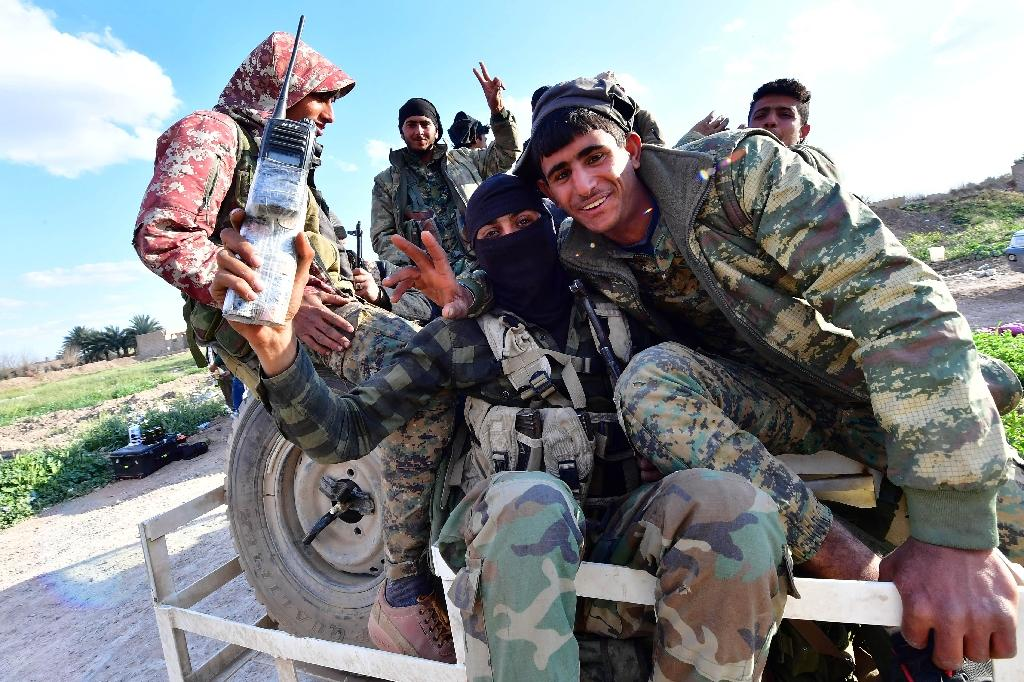Fighters of the Kurdish-led Syrian Democratic Forces make victory signs as they return from the front after delivering a killer blow to the last vestige of the Islamic State group's caliphate (AFP Photo/GIUSEPPE CACACE)