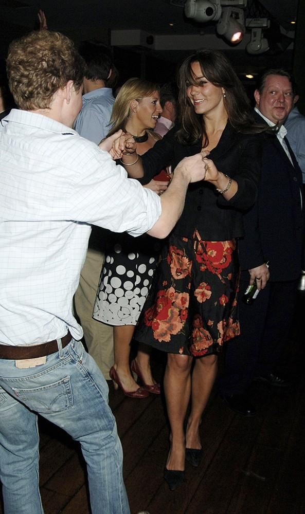 Kate dances with a friend at a pre-Wimbledon party, dressed in a dark floral dress.