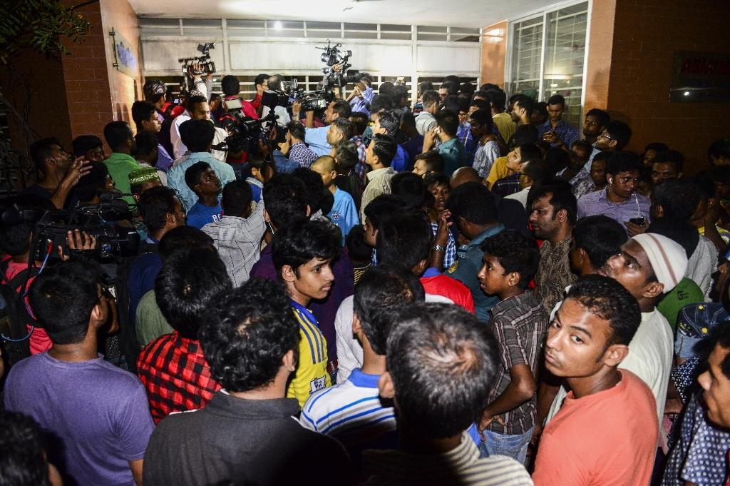Bangladeshi journalists and onlookers gather outside the apartment in Dhaka where the latest killings took place, April 25, 2016 (AFP Photo/Munir Uz Zaman)