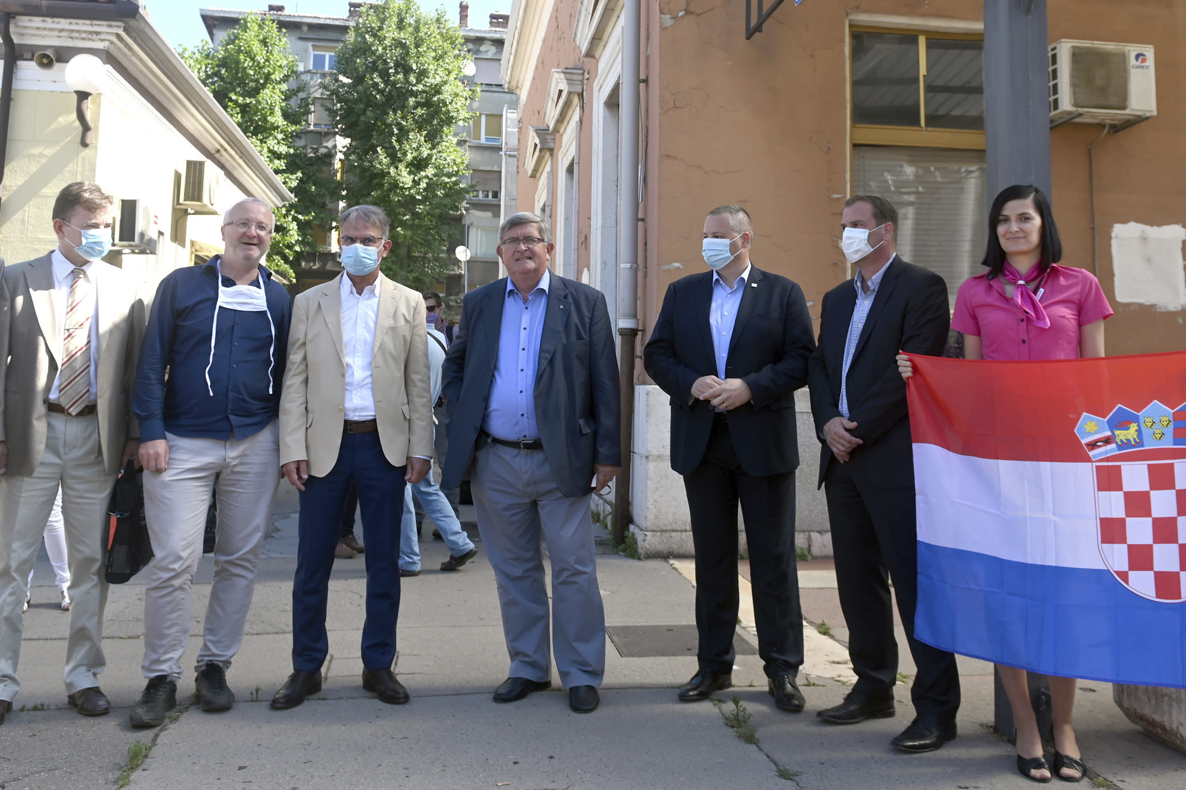 Officials including Rijeka Mayor Vojko Obersnela and Croatia's Minister of tourism Gari Capelli wait to welcome a train to arrive from the Czech Republic in Rijeka, Croatia, Wednesday, July 1, 2020. A train carrying some 500 tourists from the Czech Republic has arrived to Croatia as the country seeks to attract visitors after easing lockdown measures against the new coronavirus.(AP Photo)