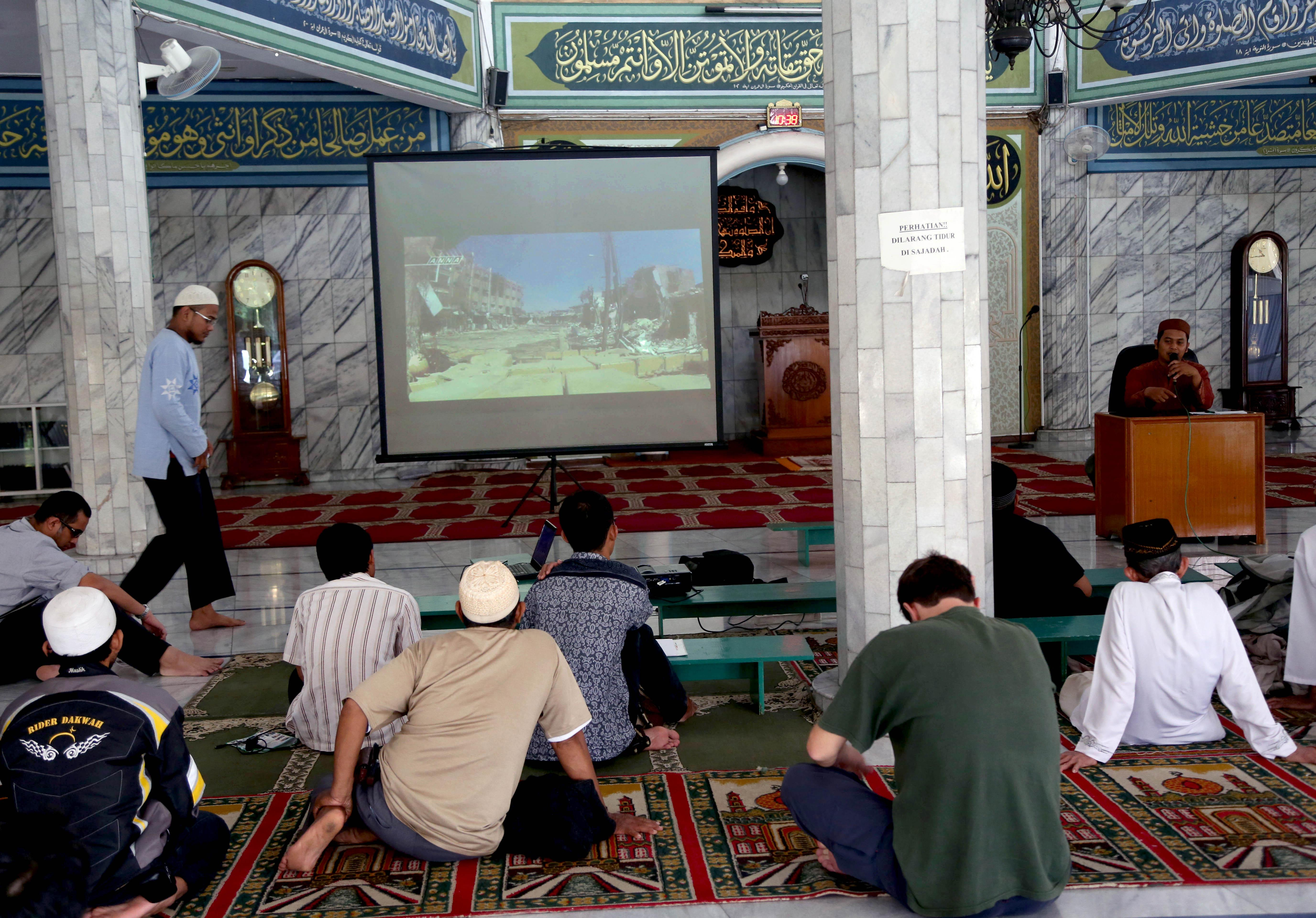 In this Sunday, Dec. 15, 2013 photo, Muslim men watch a slideshow of pictures believed to be from Syria during a prayer calling for jihad to Syria at a mosque in Jakarta, Indonesia. While security agencies in Europe and beyond are worried about militants returning from Syria, Indonesia knows only too well how foreign battlefields, training opportunities and contact with al-Qaida can lead to deadly results. Indonesian anti-terror officials estimated there were around 50 Indonesian militants fighting against the regime of Bashar Assad in Syria and the number is expected to grow. (AP Photo/Tatan Syuflana)