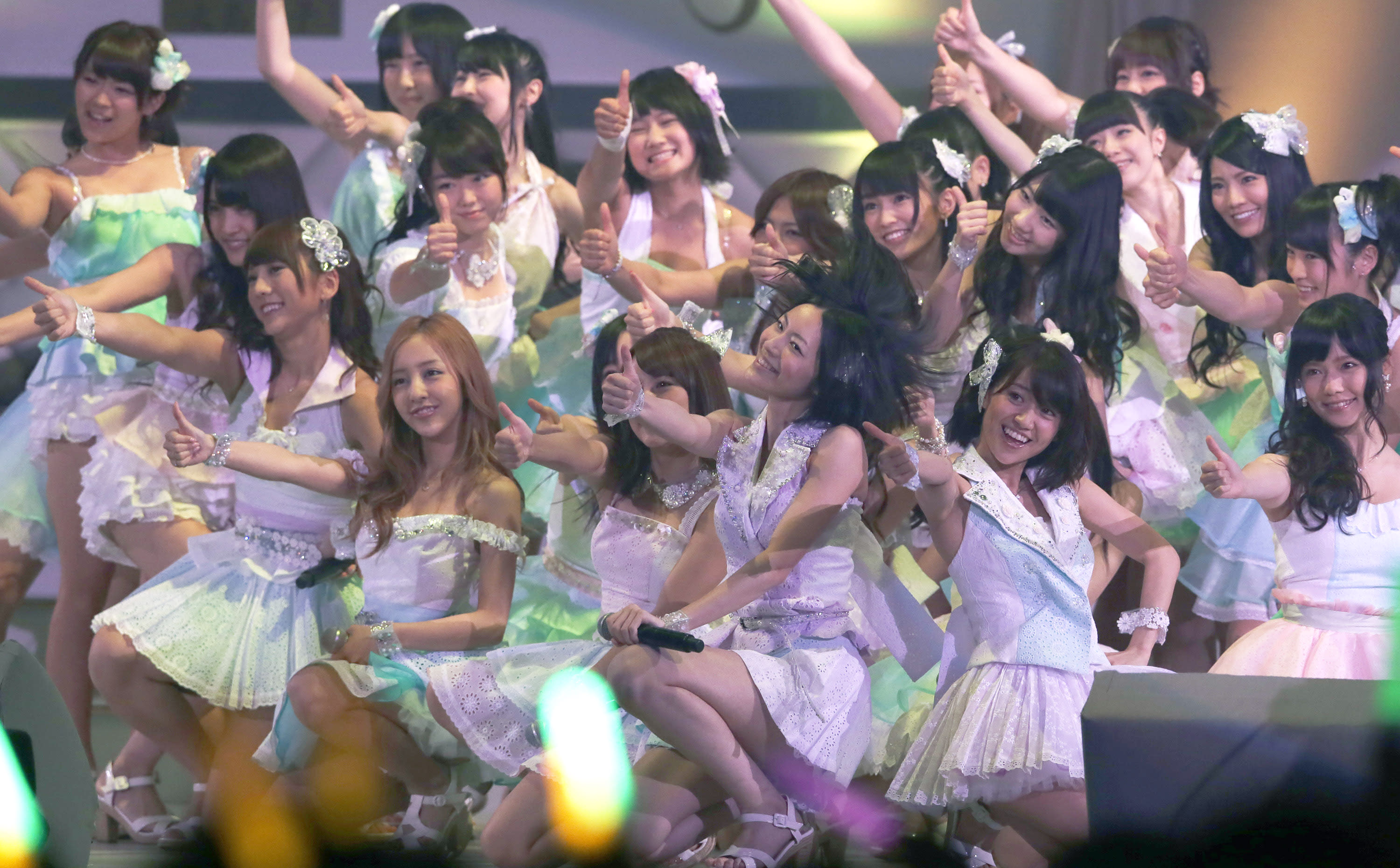 FILE - In this June 6, 2012 file photo, Japan's all-girl pop idol group AKB48 members perform during the annual AKB48 popularity poll in Tokyo. More than 60 girls and young women, split into four teams, make up what is arguably Japan's most popular pop group. It performs almost every day, has spawned affiliate groups across the country and has recently given rise to sister mega-groups in China and Indonesia. (AP Photo/Shizuo Kambayashi, File)