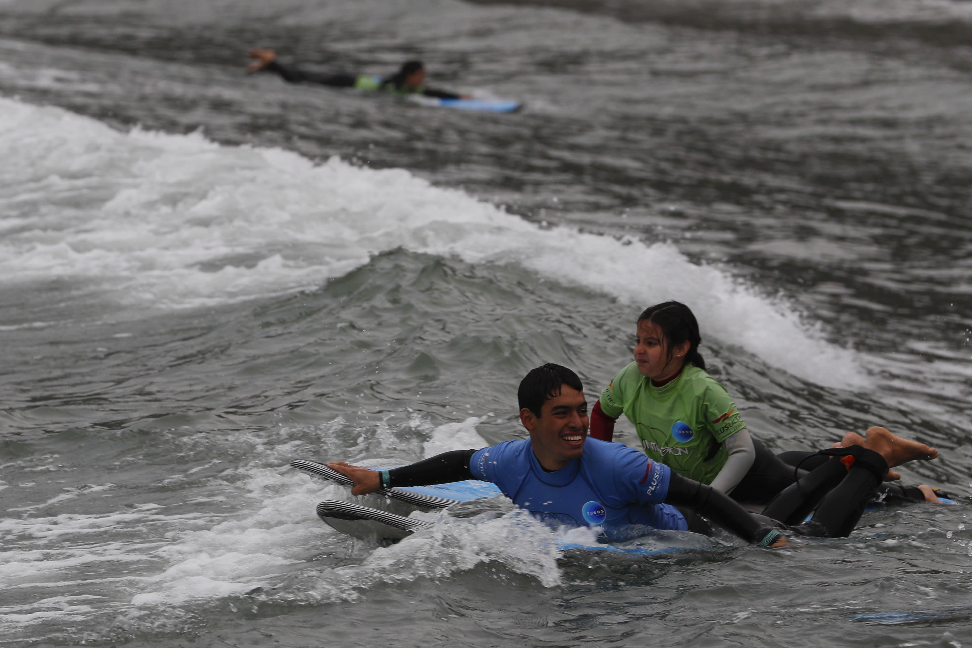 An instructor tows out a young student for a surf lesson at Barranquito beach in Lima, Peru, Thursday, July 25, 2019. Today, dozens of schools teach tourists from across the world how to ride waves at beaches with Hawaiian names in Lima's Miraflores district, while professional surfers from across the Americas prepare to compete when the sport is featured for the first time in the Pan American Games in the Peruvian capital.(AP Photo/Rebecca Blackwell)