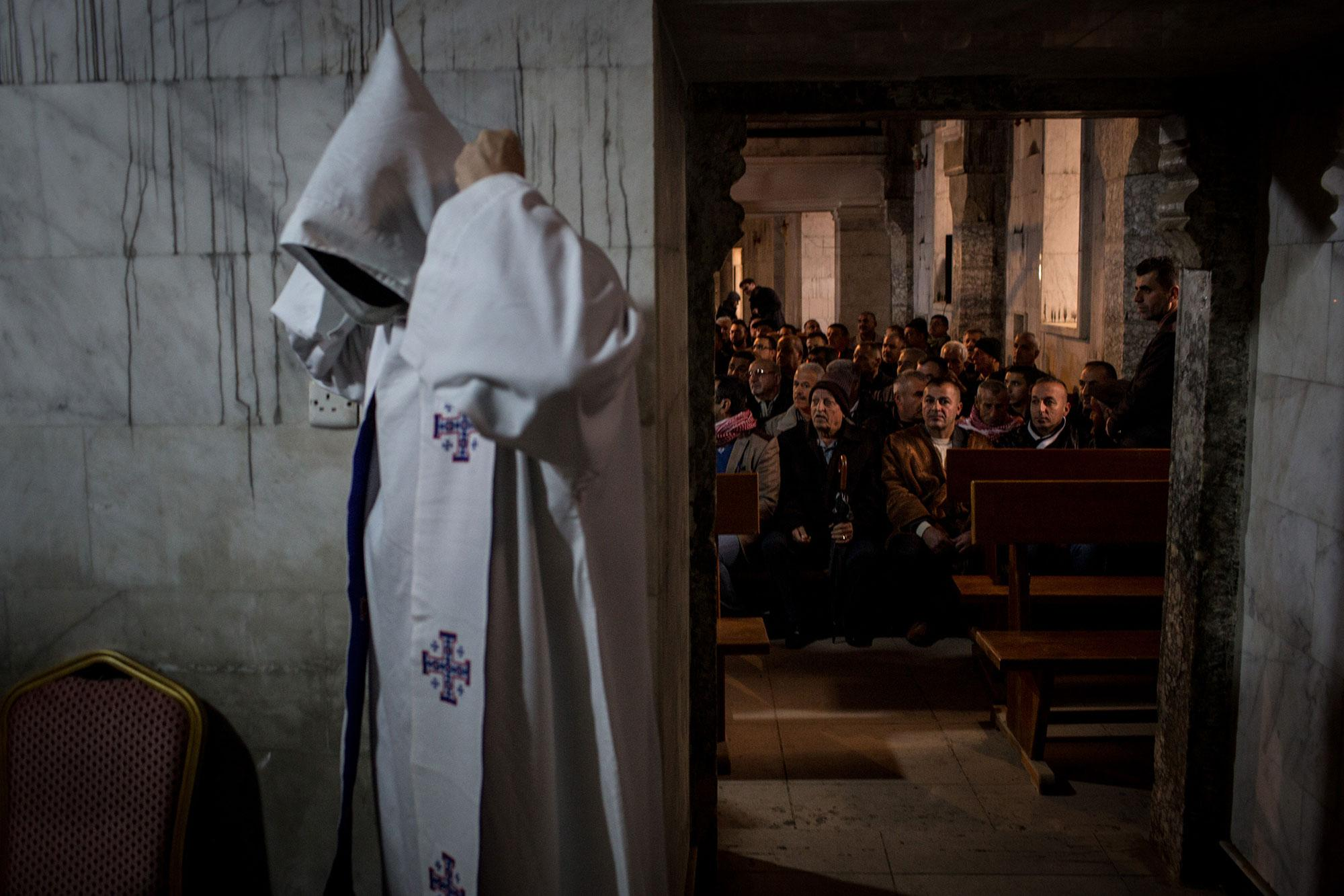 <p>People wait for the start of Christmas mass at the Mar Shimoni Church on Dec. 24, 2016 in Bartella, Iraq. The predominantly Christian town of Bartella was recently liberated from ISIL as part of the Mosul offensive. The town's four churches were heavily damaged and defaced during the two year occupation. The Christmas mass marks the first official mass in Bartella since a mass was held on Aug. 14, 2014 just hours before ISIS arrived. Christian communities around Mosul are celebrating Christmas as the Mosul offensive continues. (Photo: Chris McGrath/Getty Images) </p>