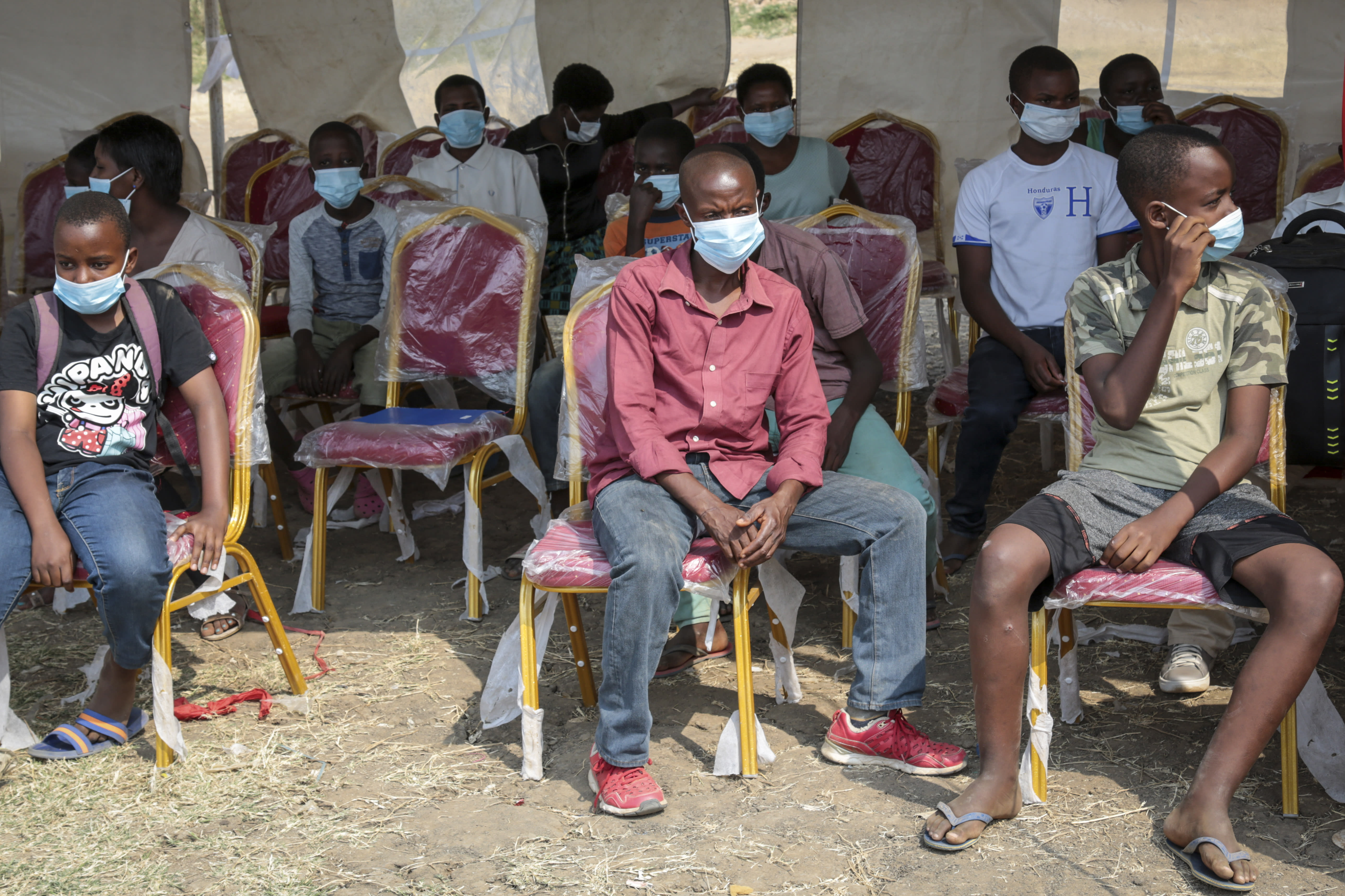 Members of the public wait to be tested for the coronavirus in Bujumbura, Burundi Monday, July 6, 2020. Burundi launched a campaign of mass screening for COVID-19 on Monday in the country's largest city Bujumbura, indicating that the new president Evariste Ndayishimiye is implementing policies to combat the spread of the disease. (AP Photo/Berthier Mugiraneza)