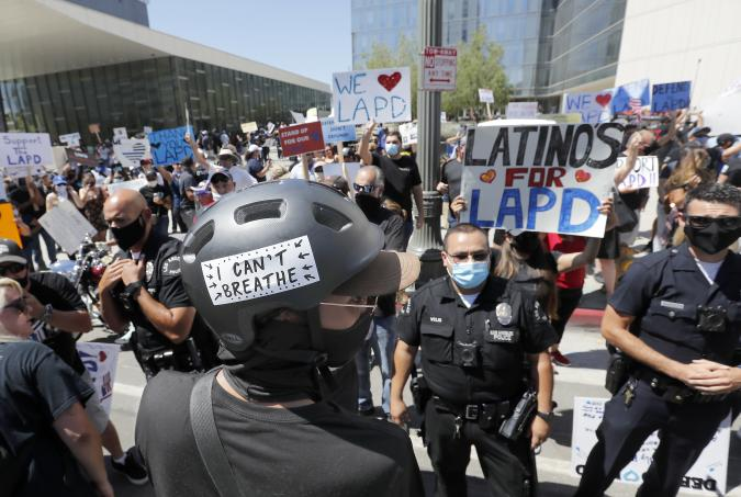 LOS ANGELES, CA - JULY 11: LAPD officers form a line to separate pro- and anti-police demonstrators outside LAPD headquarters in downtown Los Angeles on Saturday, July 11, 2020. Hundreds of cops and their supporters held a morning rally to protest a $150 million cut in the city police budget. A handful of Black Lives Matter supporters showed up to counter them. (Luis Sinco / Los Angeles Times via Getty Images)