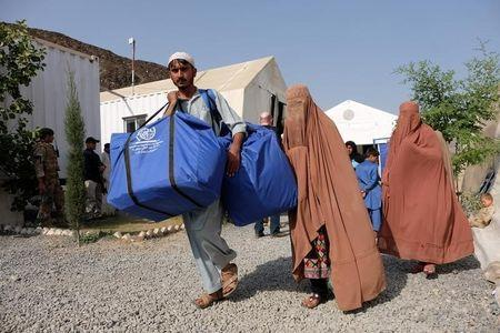 An Afghan family, who were living as refugees in Pakistan, carries bundles of supplies at a humanitarian aid station in Torkham, Afghanistan