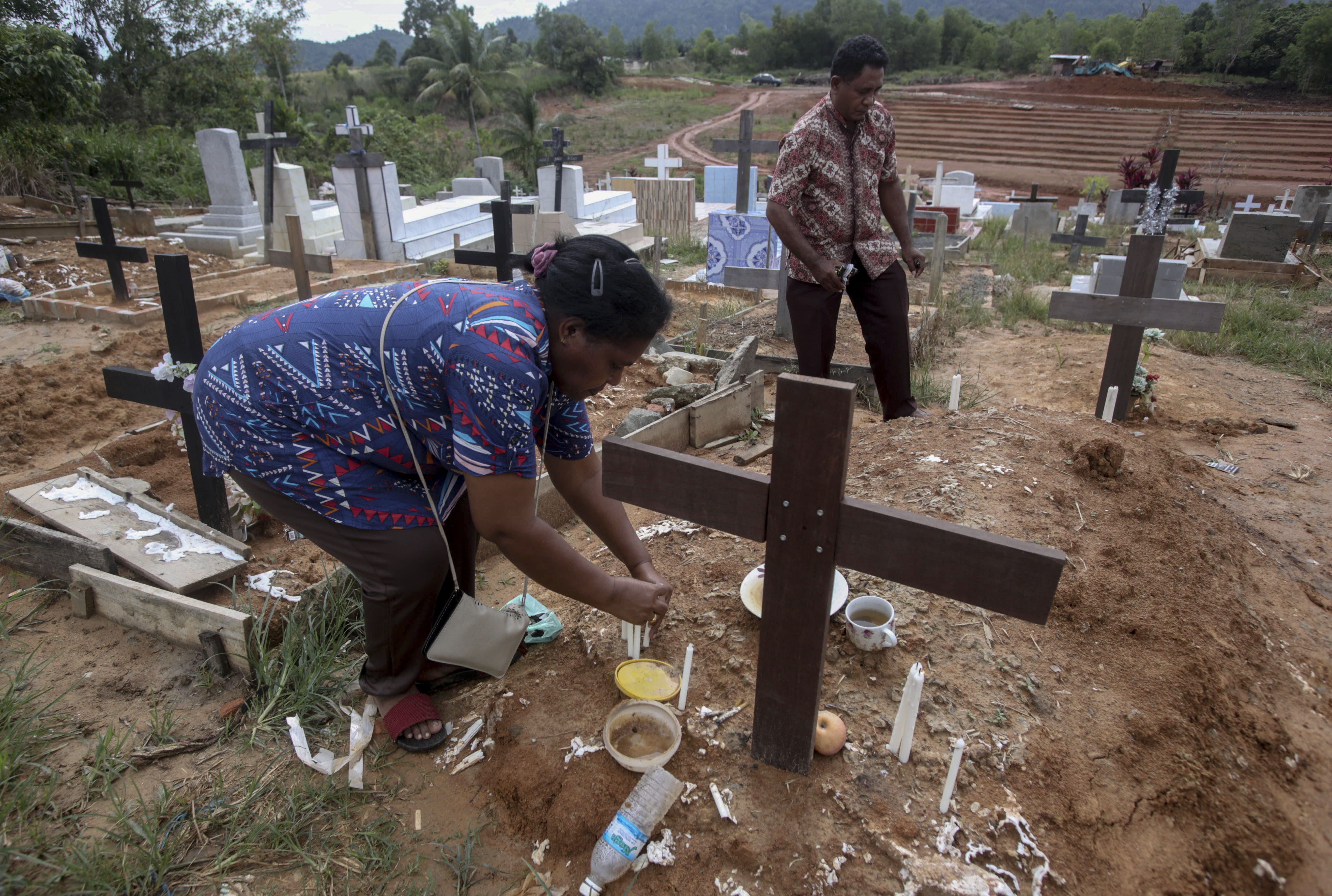 An Indonesian migrant worker places candles on the grave of her husband who worked on a Malaysian palm oil plantation in Sabah, Malaysia, on Sunday, Dec. 9, 2018. As global demand for palm oil surges, plantations are struggling to find enough laborers, frequently relying on brokers who prey on the most at-risk people. The bodies of migrants who die are sometimes not sent home. (AP Photo/Binsar Bakkara)