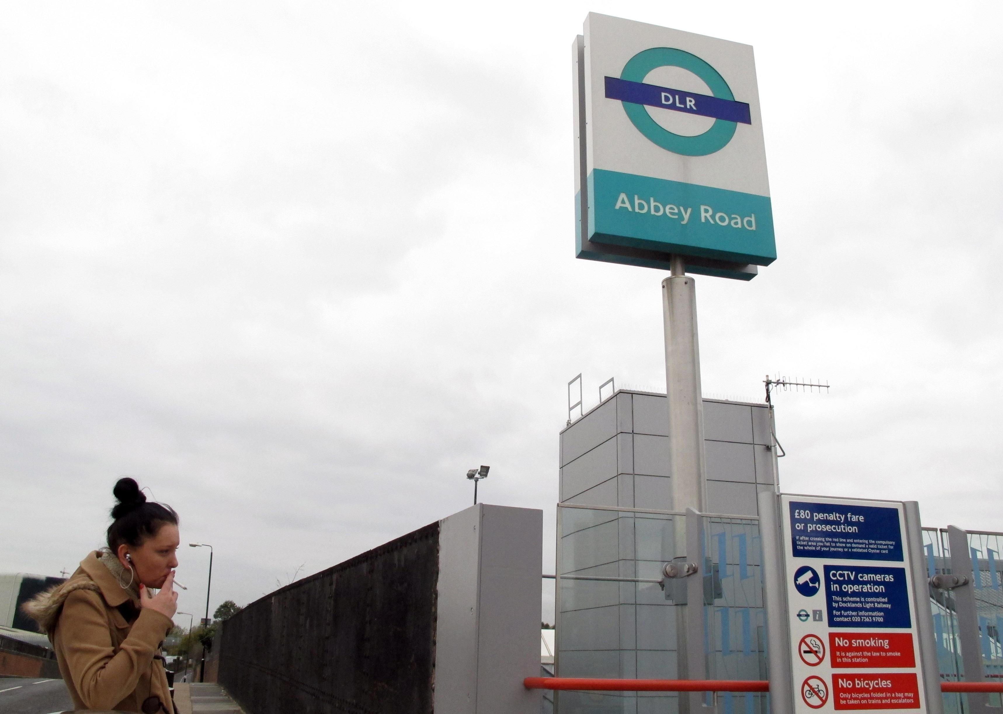 """The sign for east London's Abbey Road Station is seen against the backdrop of apartment buildings on Friday, Nov. 10, 2012. Abbey Road Station is more than nine miles from the striped crosswalk made famous by the Beatles album """"Abbey Road,"""" but this drab transit hub keeps drawing confused fans of the Fab Four into unwanted jaunts through a gritty, industrial area of east London. (AP Photo/Raphael Satter)"""