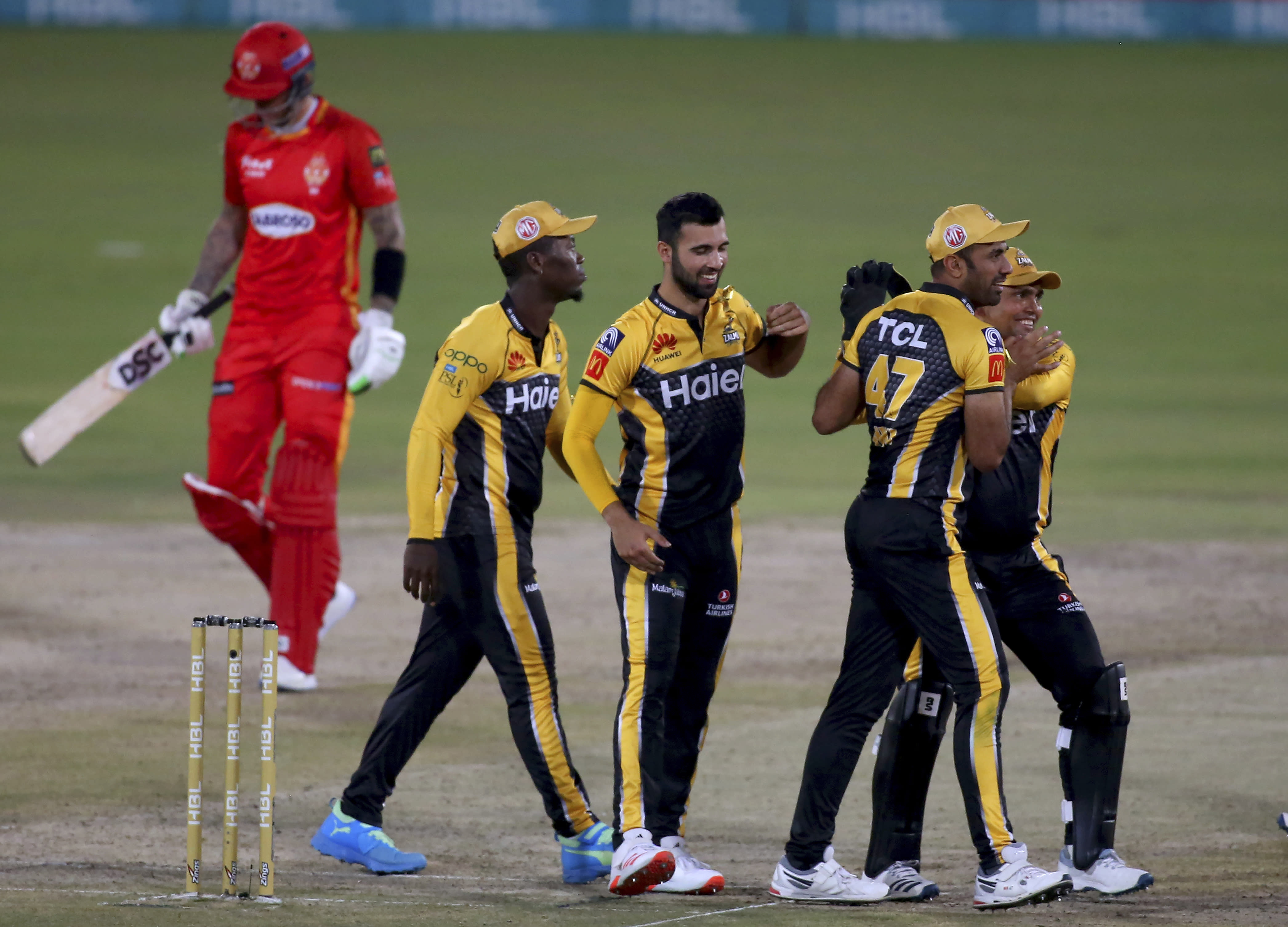 Peshawar Zalmi' Saqib Mahmood, center, celebrates with teammates after taking the wicket of Islamabad United' Alex Hales, left, during a Pakistan Super League T20 cricket match between Islamabad United and Peshawar Zalmi at the National Stadium, in Karachi, Pakistan, Saturday, Feb. 27, 2021. (AP Photo/Fareed Khan)