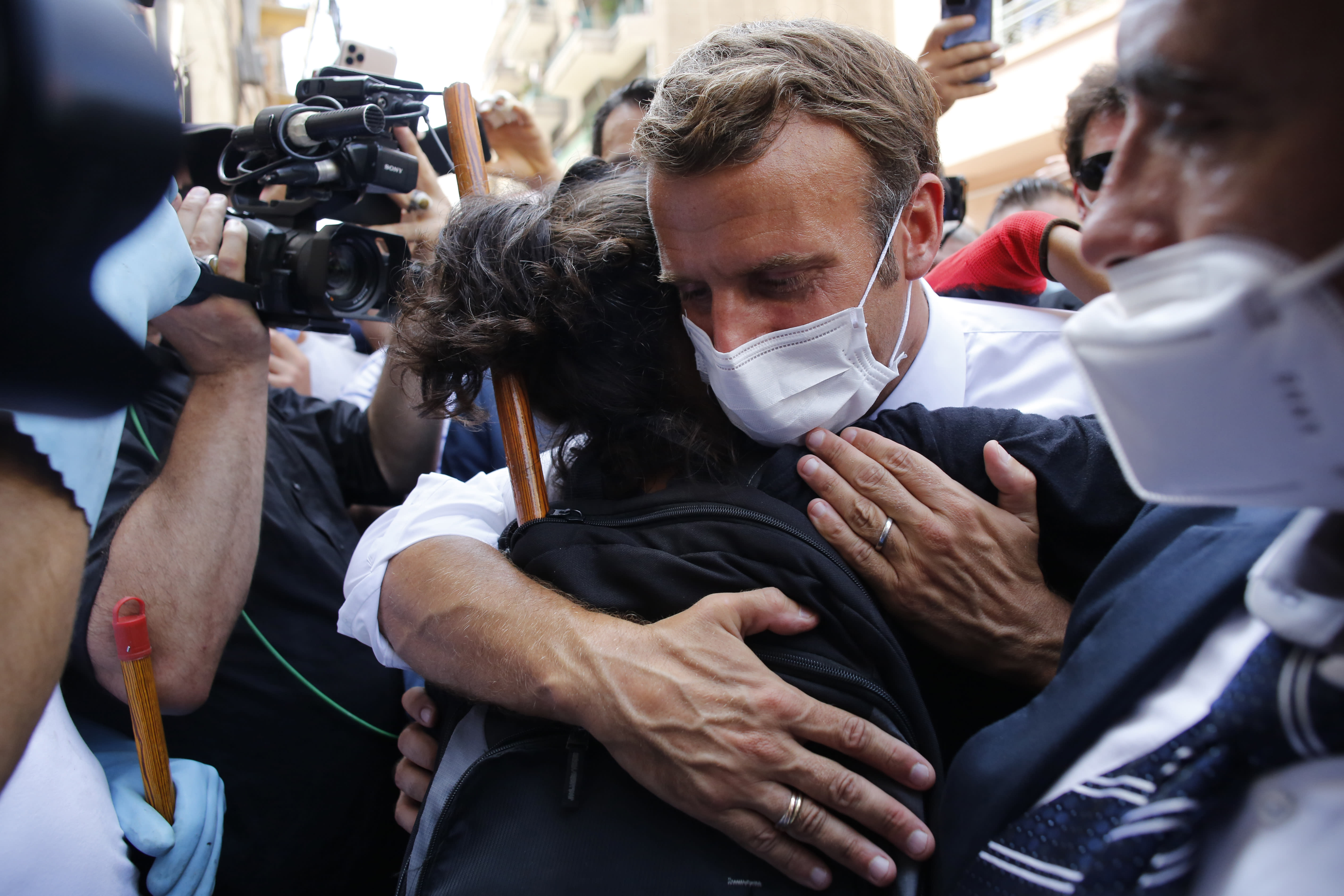 FILE - In this Aug. 6, 2020, file photo, French President Emmanuel Macron hugs a resident as he visits a devastated street of Beirut, Lebanon. In the wake of Beirut's massive port explosion, Macron has taken a tough line, setting deadlines for Lebanon's politicians to carry out reforms. His hands-on approach has angered some in Lebanon and brought praise from others. (AP Photo/Thibault Camus, Pool)