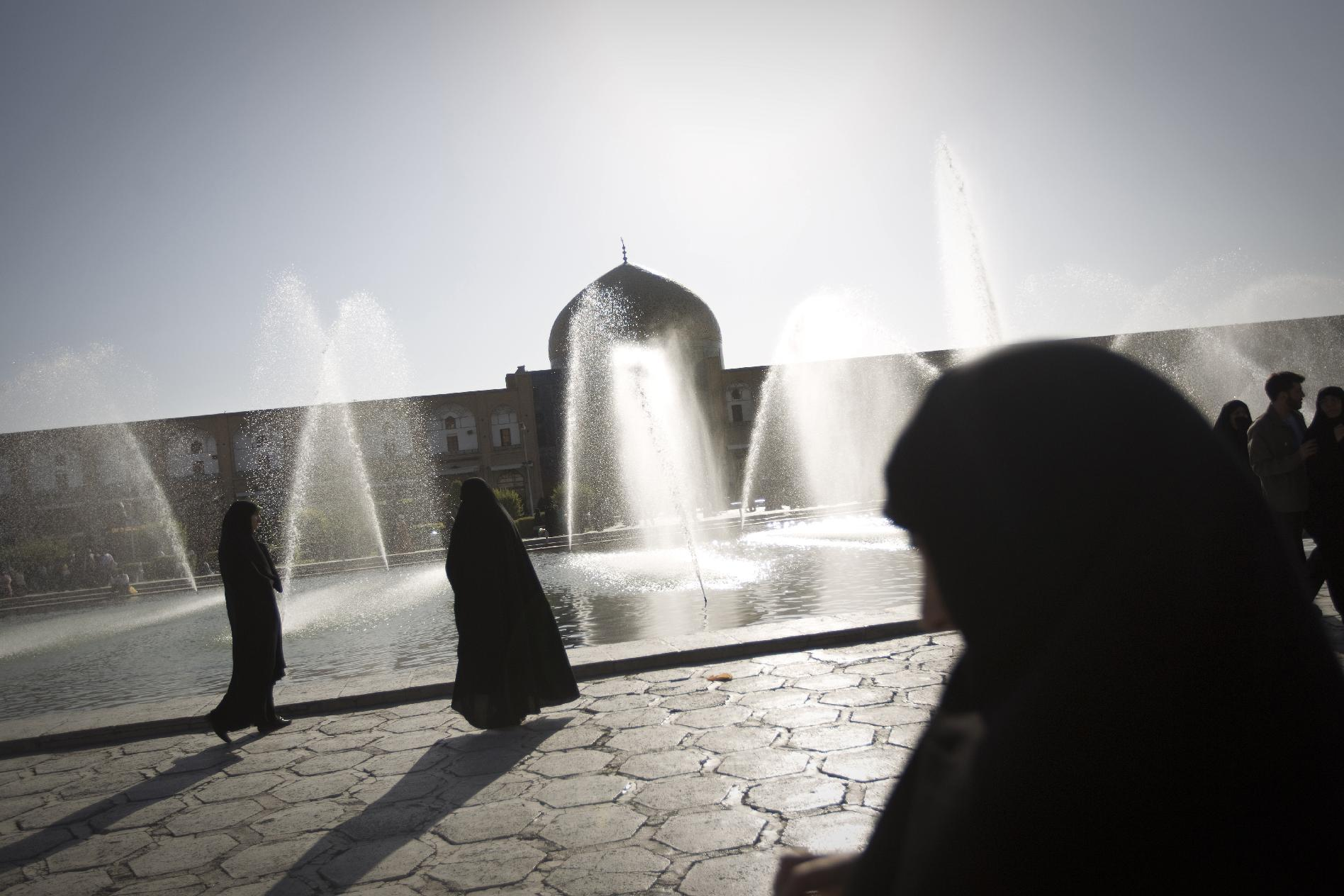 Veiled Iranian women walk past water fountains in the historical Naqsh-e Jahan Square in Isfahan on August 31, 2011