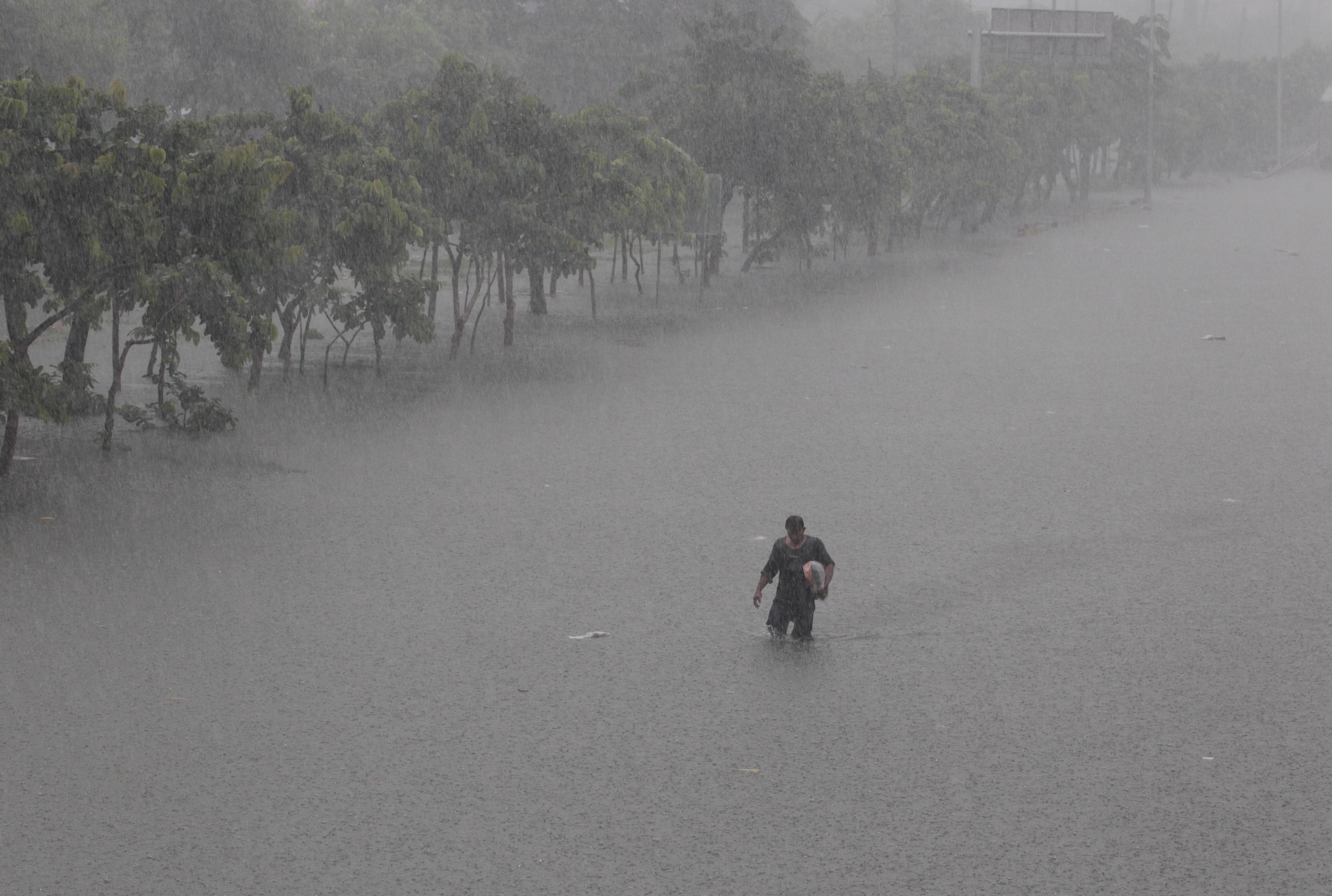 A Filipino man crosses a flooded highway at the financial district of Makati, south of Manila, Philippines on Tuesday, Aug. 20, 2013. Flooding caused by some of the Philippines' heaviest rains on record submerged more than half the capital Tuesday, turning roads into rivers and trapping tens of thousands of people in homes and shelters. The government suspended all work except rescues and disaster response for a second day. (AP Photo/Aaron Favila)