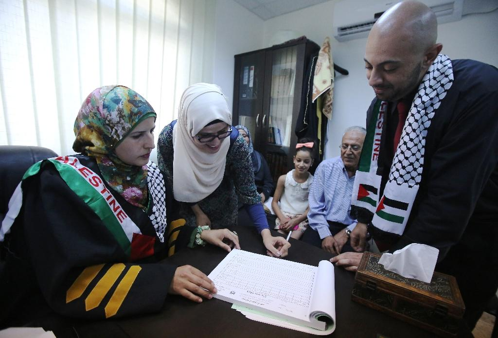 Tahrir Hamad (left), the first Palestinian woman justice of the peace, pronounces Thaer (right) and Rawan (2nd left) man and wife (AFP Photo/Abbas Momani)