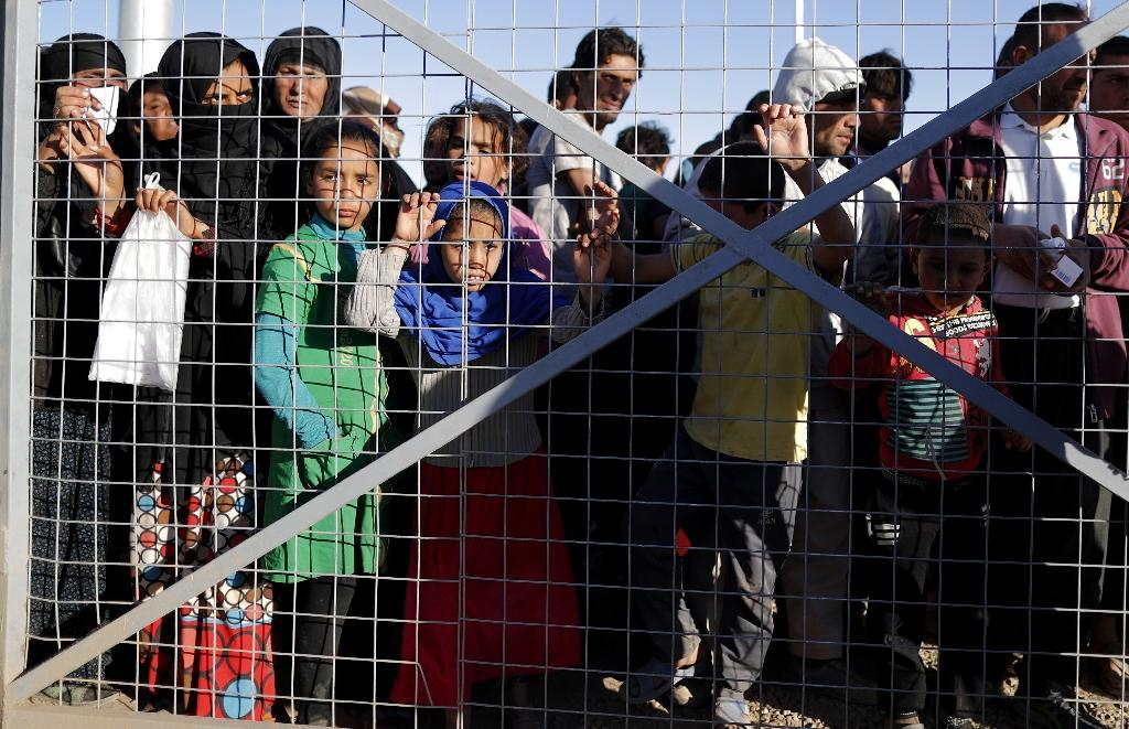 Iraqi refugees wait behind a fenced gate for food distribution at the Khazir refugee camp near the Kurdish checkpoint of Aski Kalak, 40 km west of Arbil, the capital of the autonomous Kurdish region of northern Iraq, on November 21, 2016 (AFP Photo/Thomas Coex)