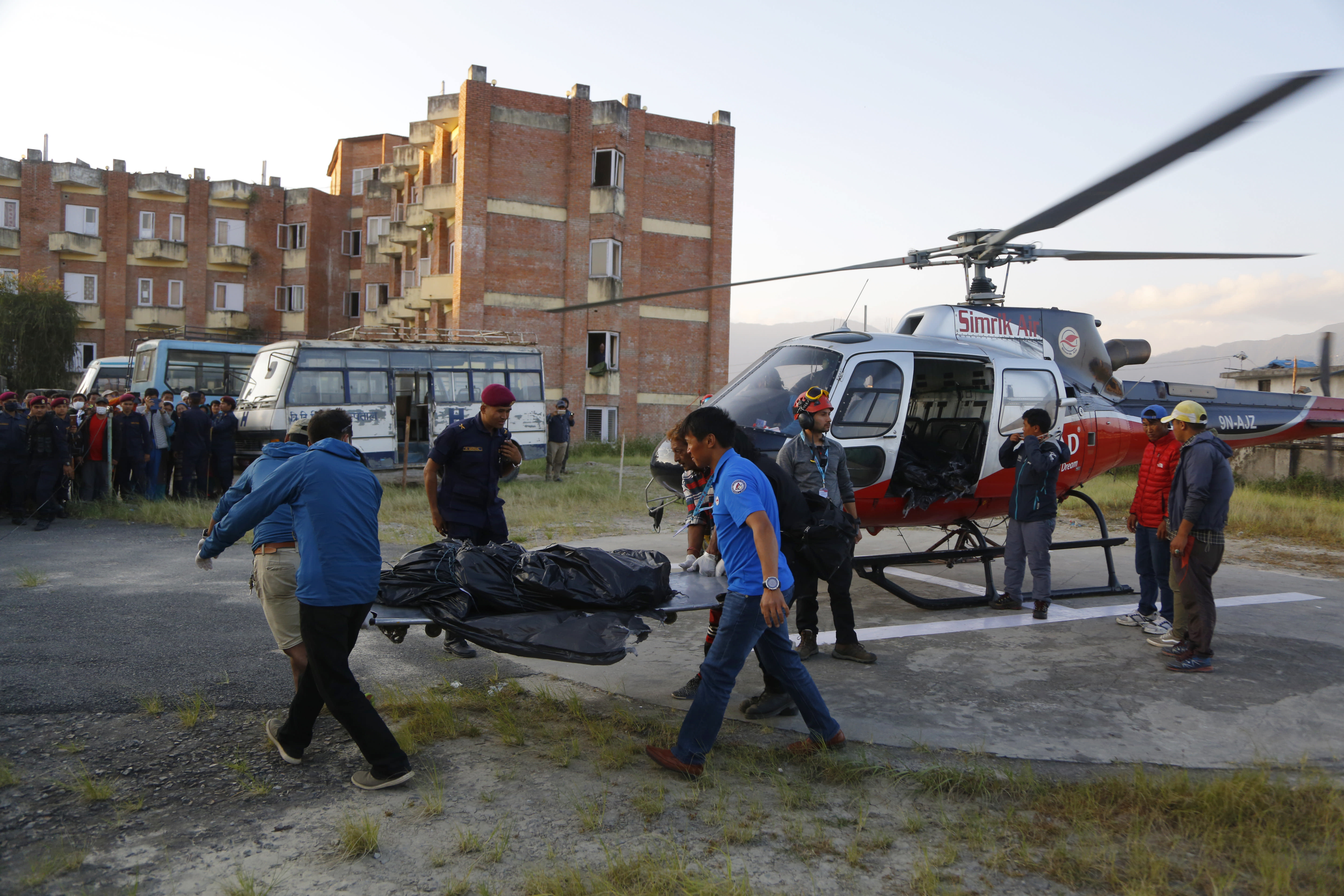 Officials unload the bodies after a helicopter carrying bodies of those killed in Gurja Himal mountain arrives at the Teaching hospital in Kathmandu, Nepal, Sunday, Oct. 14, 2018. Rescuers retrieved the bodies of five South Korean climbers and their four Nepalese guides from Gurja Himal mountain, where they were killed when their base camp was swept by a strong storm. (AP Photo/Niranjan Shrestha)