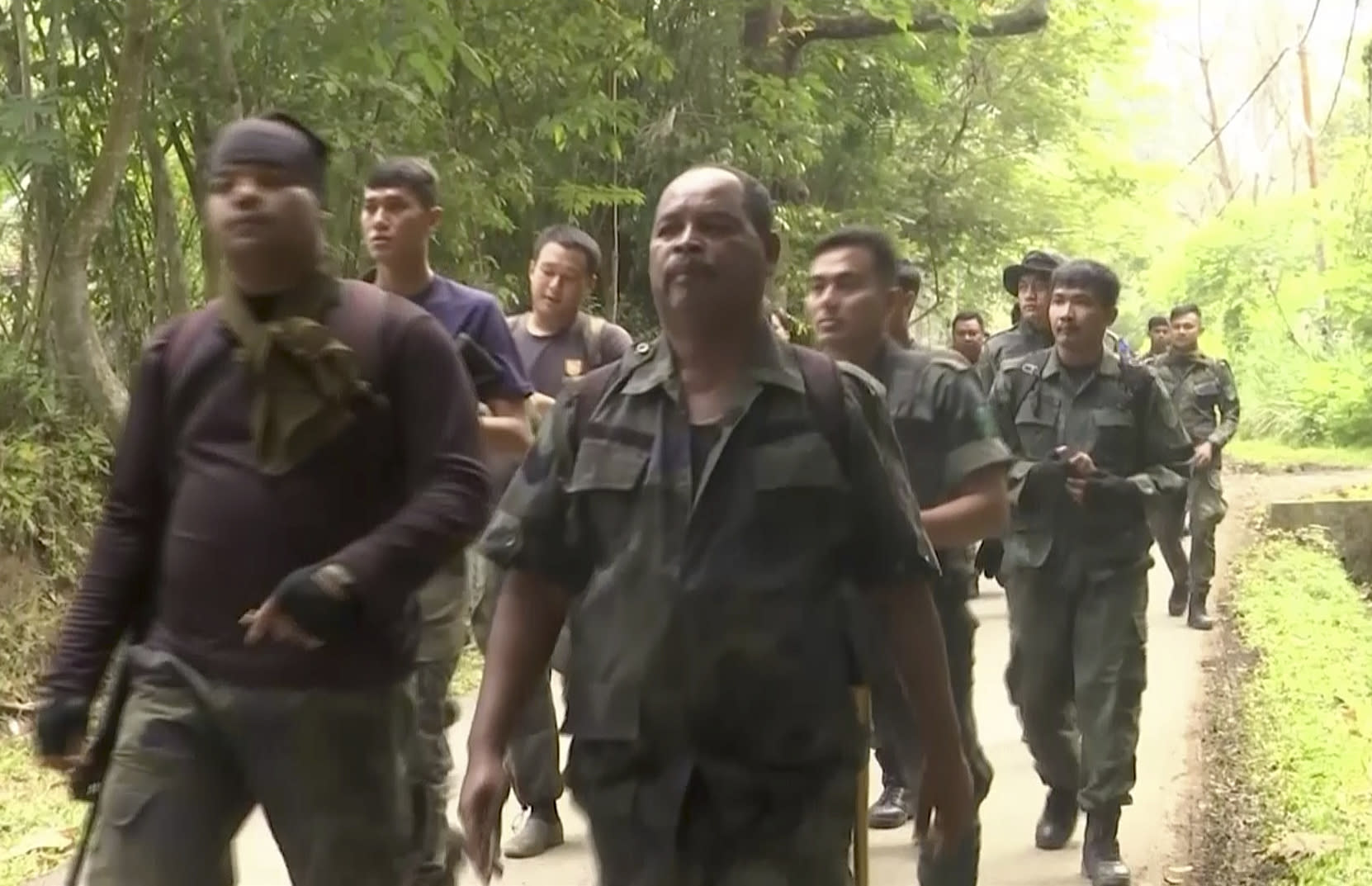 In this image from a video, rescuers walk in plantation as they conduct a search and rescue operation for a missing British girl at a forest in Seremban, Malaysia Tuesday, Aug. 13, 2019. Malaysian police say rescuers have found the body of a Caucasian female in the forest surrounding a nature resort where a 15-year-old London girl was reported missing more than a week ago. State police chief says officials are in the process of determining whether the body, which was found on Tuesday, is Nora Anne Quoirin. (AP Photo)