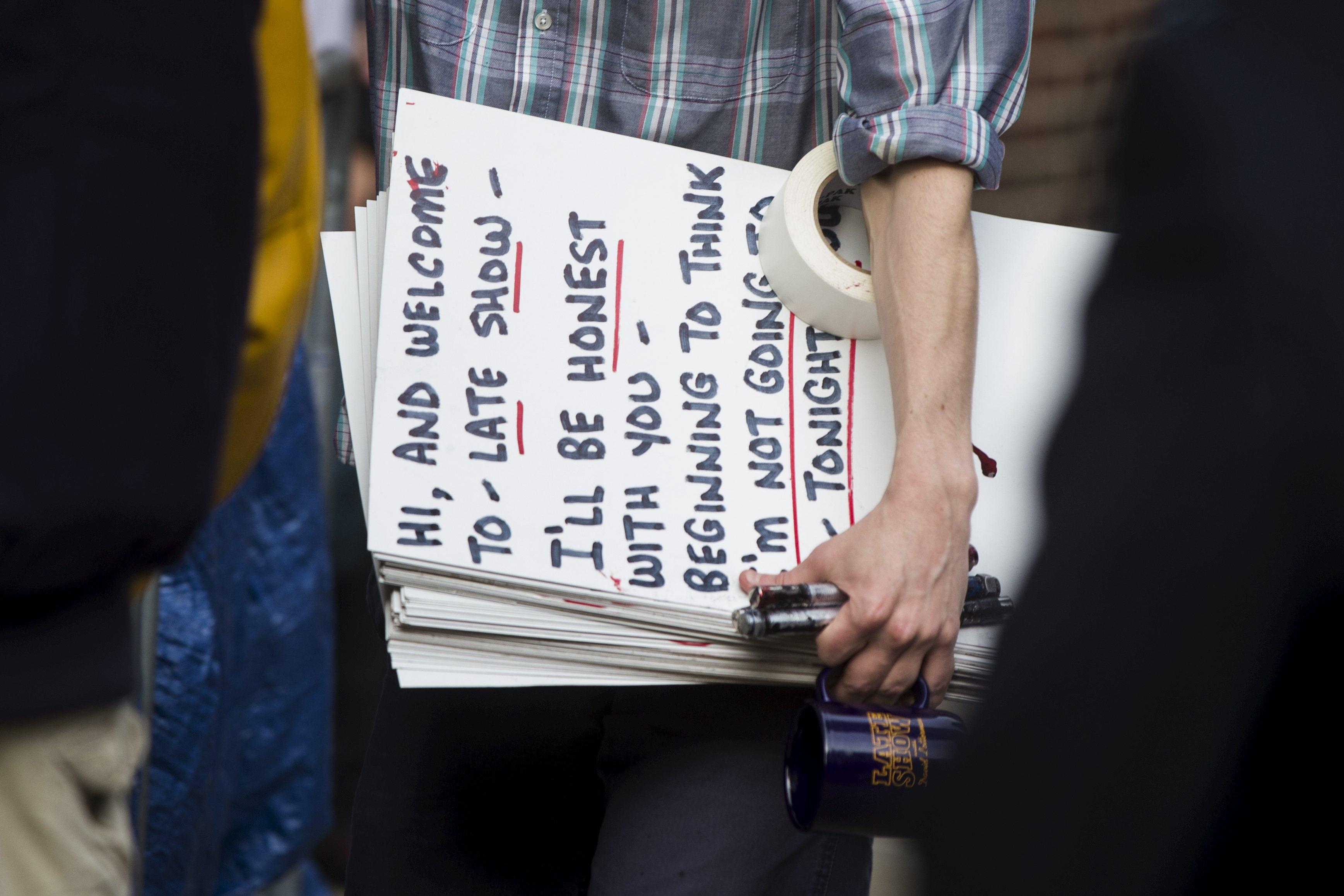 """A man carries a cue card for David letterman outside the Ed Sullivan Theater in Manhattan after the taping of tonight's final edition of """"The Late Show"""" with David Letterman in New York May 20, 2015. REUTERS/Lucas Jackson"""