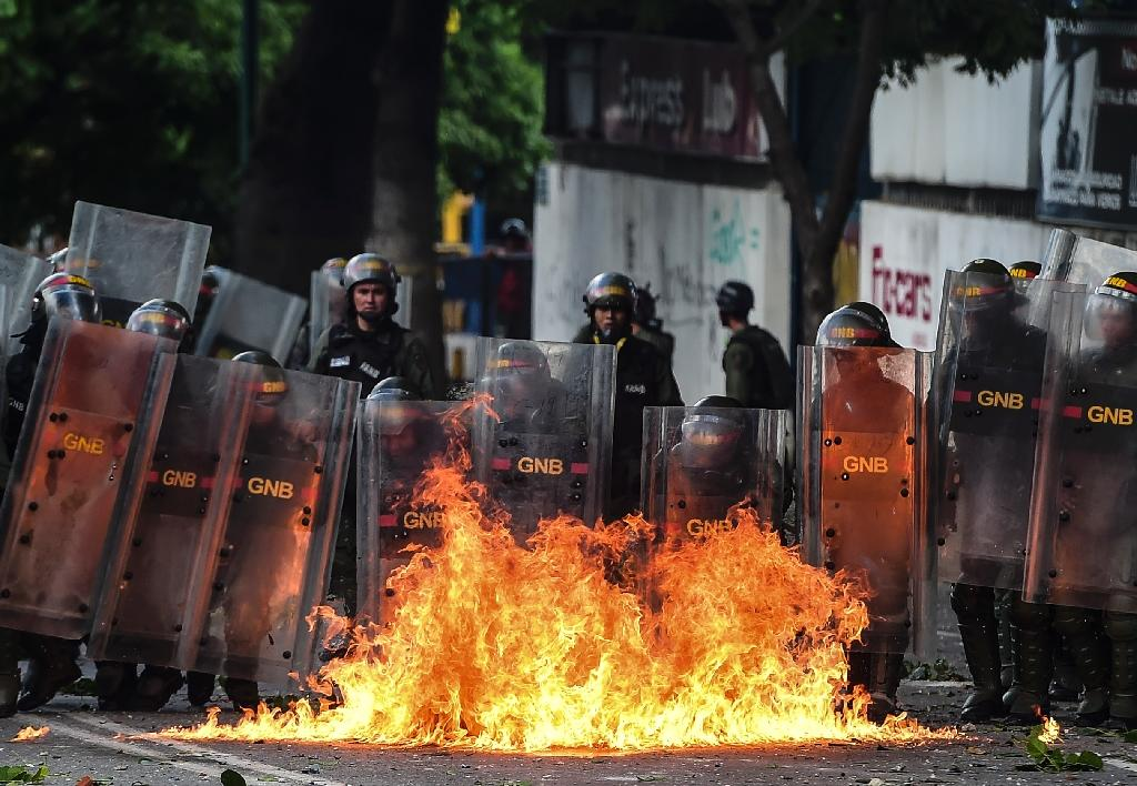 Members of Venezuela's National Guard use their shields to form a barrier from a fire during clashes with anti-government demonstrators in Caracas (AFP Photo/RONALDO SCHEMIDT)