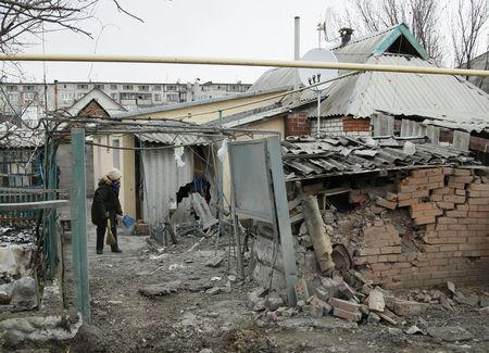 A woman cleans up debris near her house damaged by recent shelling in the rebel-held town of Yasynuvata