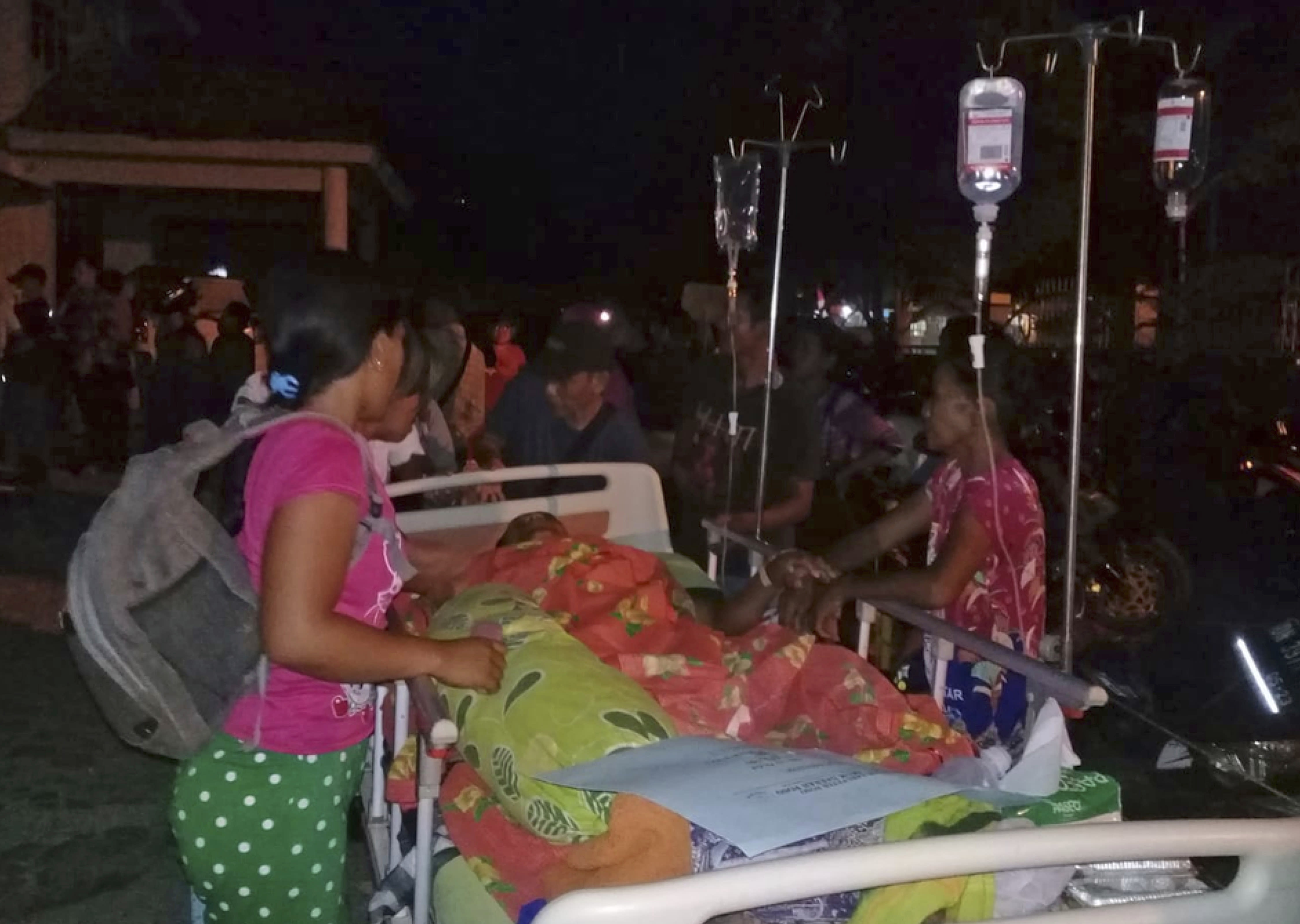 Patients are evacuated from a hospital following a strong earthquake in Poso, central Sulawesi, Indonesia, Friday, Sept. 28, 2018. Powerful earthquakes jolted the Indonesian island of Sulawesi on Friday, damaging houses and briefly triggered a tsunami warning. (AP Photo/Yoanes Litha)