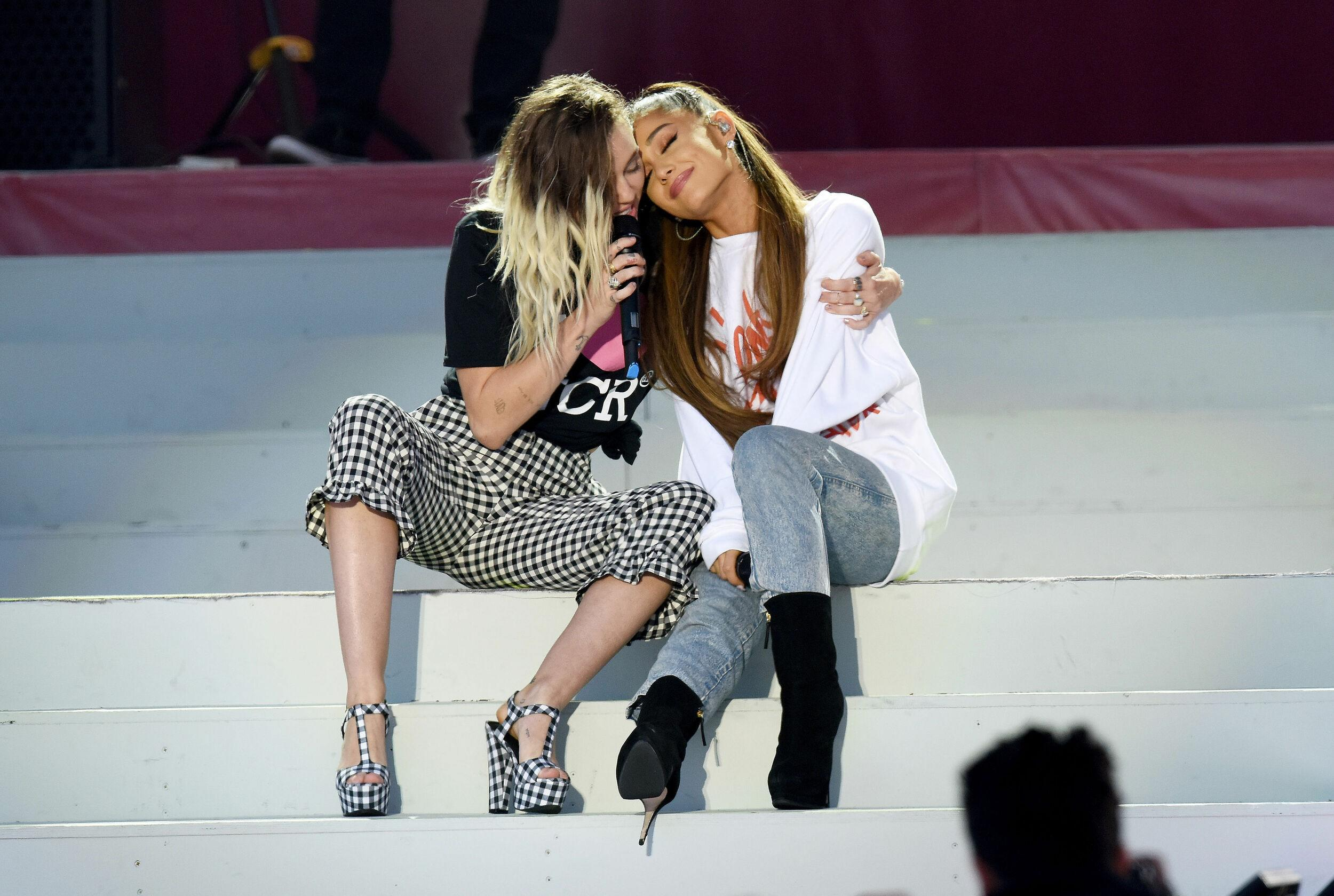 NO SALES. Free for editorial use. Handout photo issued by One Love Manchester of Miley Cyrus (left) and Ariana Grande (right) during the One Love Manchester benefit concert for the victims of the Manchester Arena terror attack at Emirates Old Trafford, Greater Manchester.