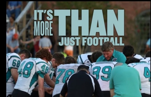 High school football coach Ronnie Mitchem (pictured in front of No. 99) was at the center of a national conversation over protest and the national anthem. (Photo via Victory & Praise Christian Academy)