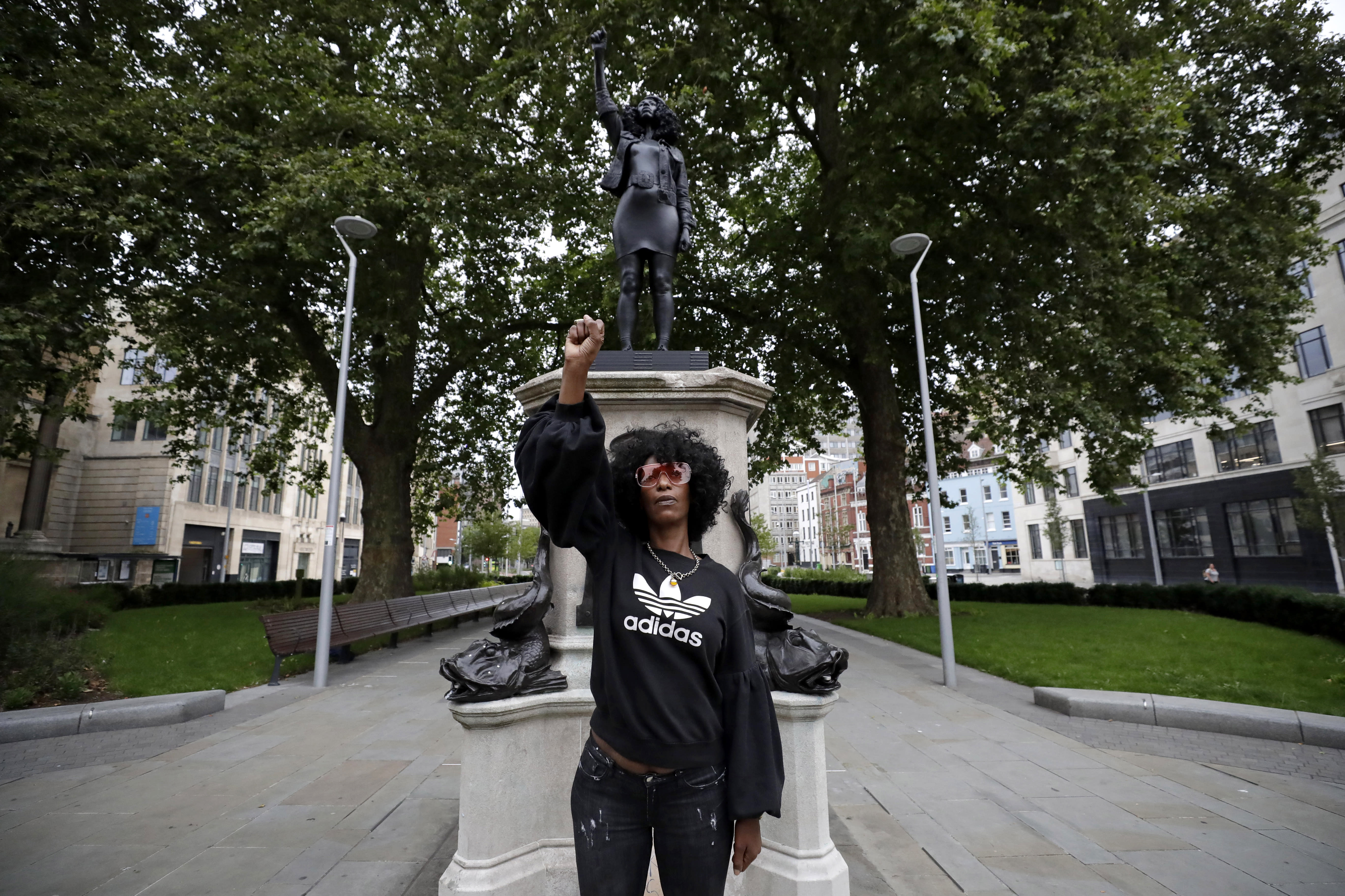 """Jen Reid poses for photographs in front of the new black resin and steel statue portraying her, entitled """"A Surge of Power (Jen Reid) 2020"""" by artist Marc Quinn after the statue was put up this morning on the empty plinth of the toppled statue of 17th century slave trader Edward Colston, which was pulled down during a Black Lives Matter protest in Bristol, England, Wednesday, July 15, 2020. On June 7 anti-racism demonstrators pulled the 18-foot (5.5 meter) bronze likeness of Colston down, dragged it to the nearby harbor and dumped it in the River Avon — sparking both delight and dismay in Britain and beyond. (AP Photo/Matt Dunham)"""