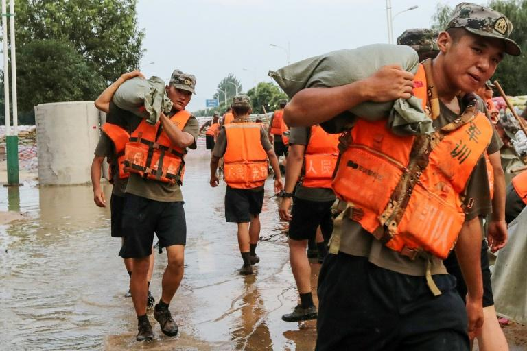 State media reported that more than 100,000 people -- including rescue personnel, soldiers, and ordinary citizens -- had been thrown into flood-control efforts in Jiangxi (AFP Photo/STR)