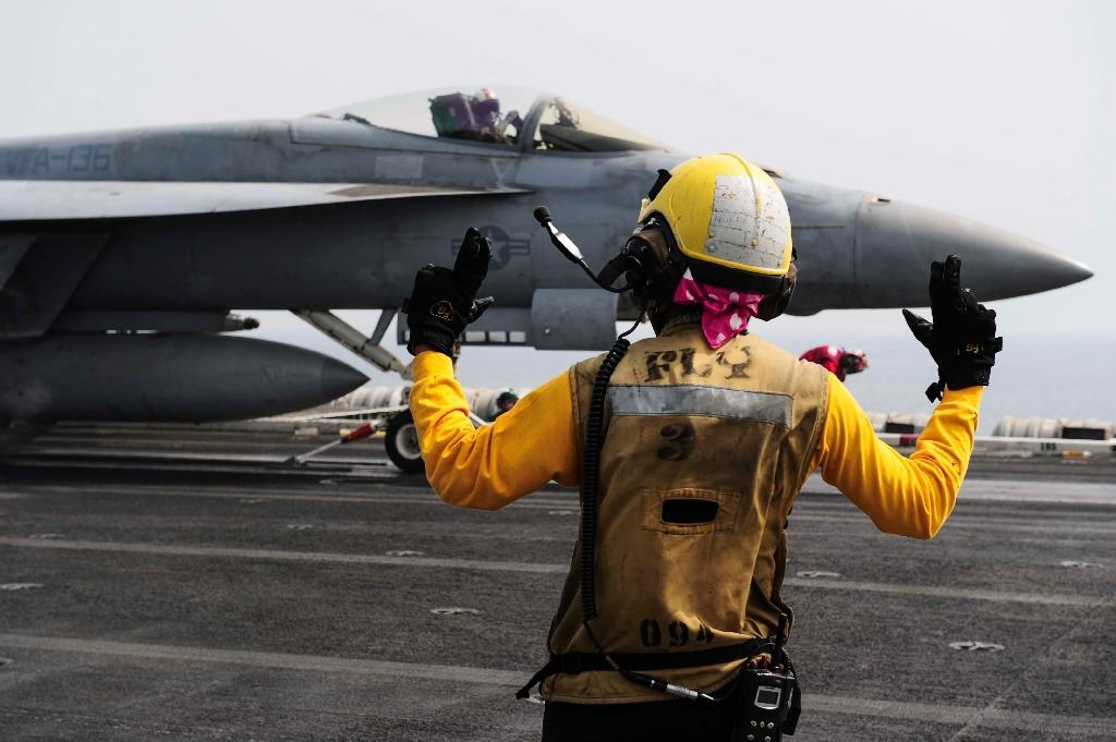 An aircraft handler directs an F/A-18E Super Hornet on the flight deck on board the aircraft carrier USS Theodore Roosevelt (CVN 71) (AFP Photo/MCS1 Anna Van Nuys )