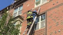 Firefighters Helps Elderly Woman Down a Ladder as Fire Rages