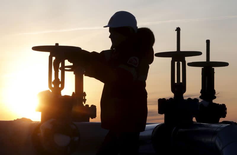 Worker checks valve of oil pipe at Lukoil company owned Imilorskoye oil field outside West Siberian city of Kogalym