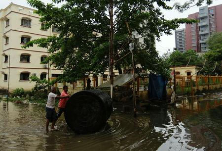 Men push a water tank through a partially flooded street at a residential area in Mumbai, India, August 30, 2017. REUTERS/Danish Siddiqui