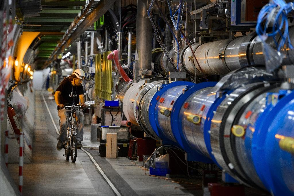 A worker rides his bicycle in a tunnel of the European Organisation for Nuclear Research (CERN) Large Hadron Collider during maintenance works in Meyrin, Switzerland on July 19, 2013 (AFP Photo/Fabrice Coffrini)