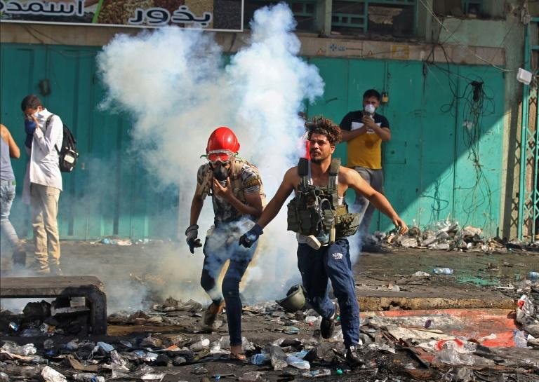 Iraqi protesters run from tear gas during clashes with security forces at Baghdad's Khallani Square (AFP Photo/AHMAD AL-RUBAYE)