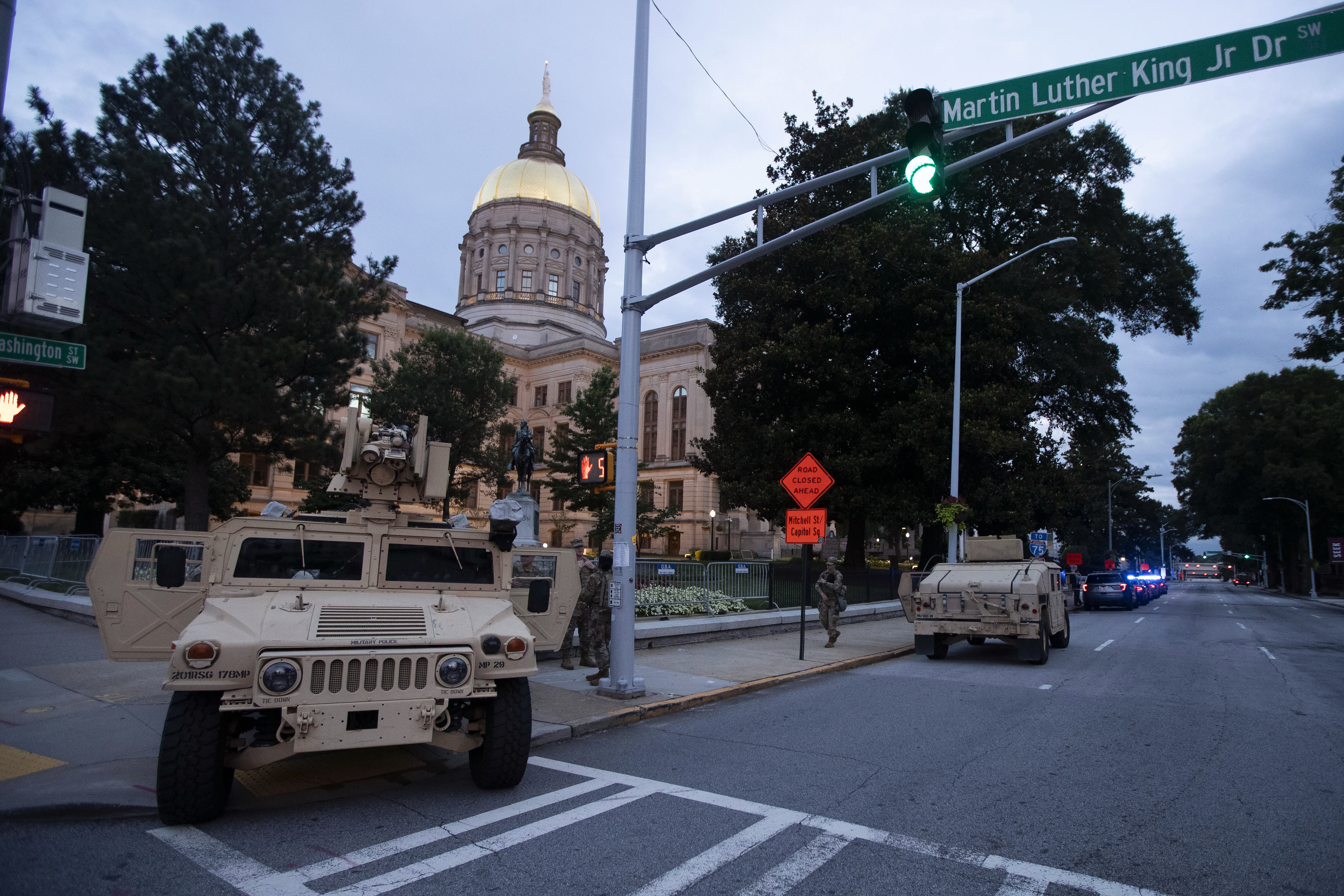 Members of the Georgia National Guard stand outside the State Capitol on Tuesday, July 7, 2020, in Atlanta. Georgia Gov. Brian Kemp mobilized the guard after a surge in gun violence over the weekend. (AP Photo/John Bazemore)