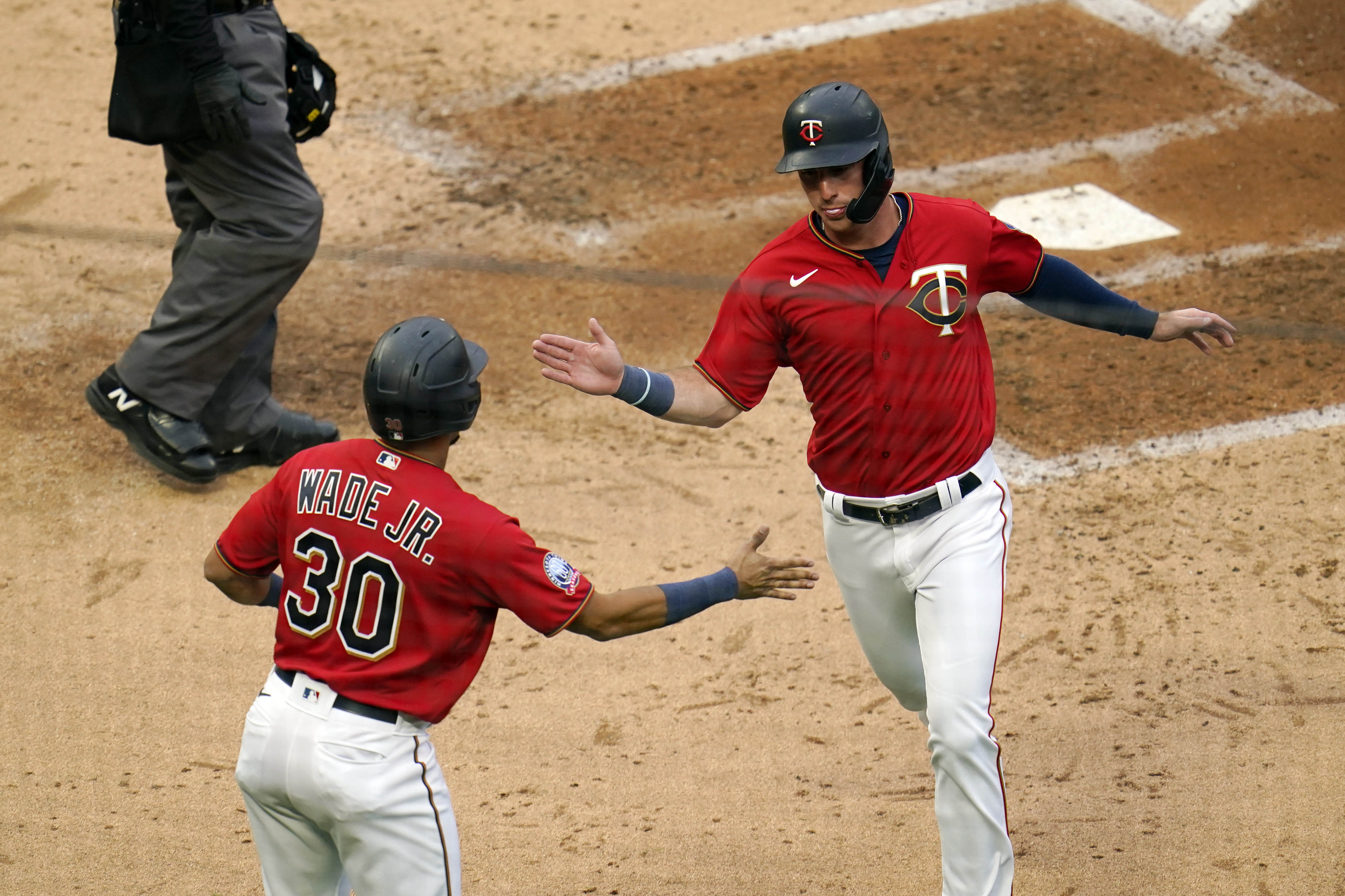 Minnesota Twins' LaMonte Wade, Jr., left, greets Brent Rooker after they both scored on a bases loaded double by Eddie Rosario off Detroit Tigers pitcher Daniel Norris in the third inning of a baseball game Monday, Sept. 7, 2020, in Minneapolis. (AP Photo/Jim Mone)