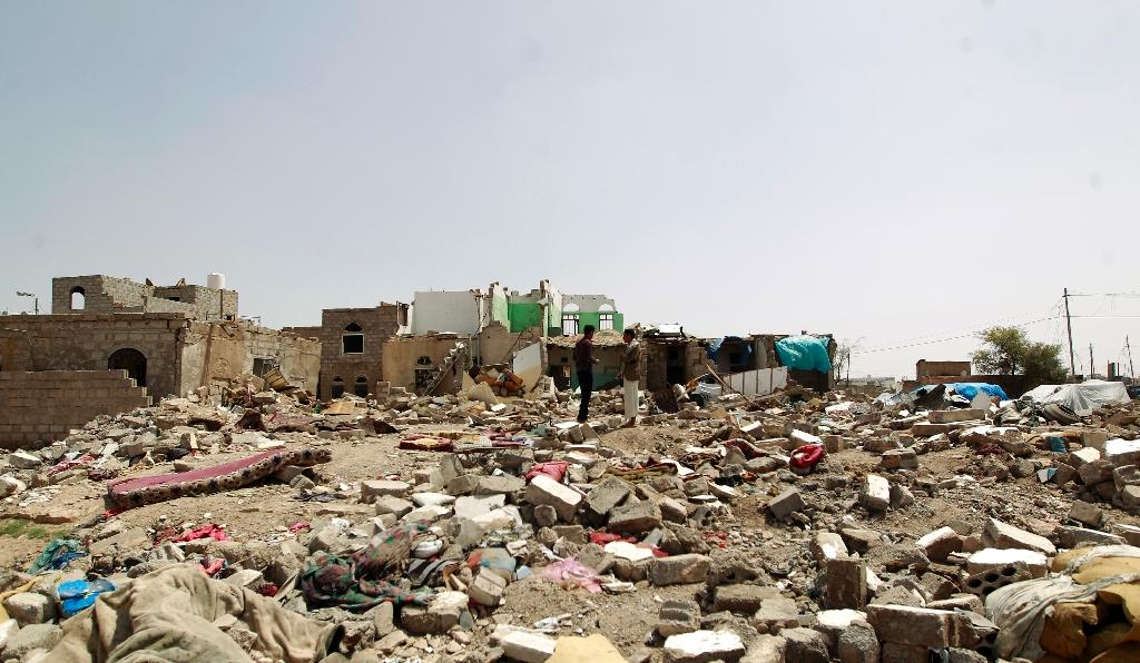 Yemenis walk amidst the rubble of houses destroyed by Saudi-led air strikes on a residential area in Sanaa, on May 18, 2015