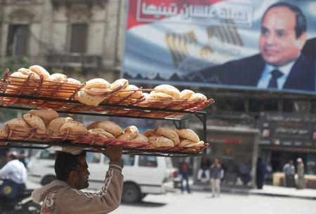 A man carries breads on his head along a busy street near a banner for Egypt's President Abdel Fattah al-Sisi after election results in Cairo